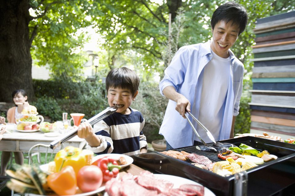 Boy sneaks food while dad cooks on a grill
