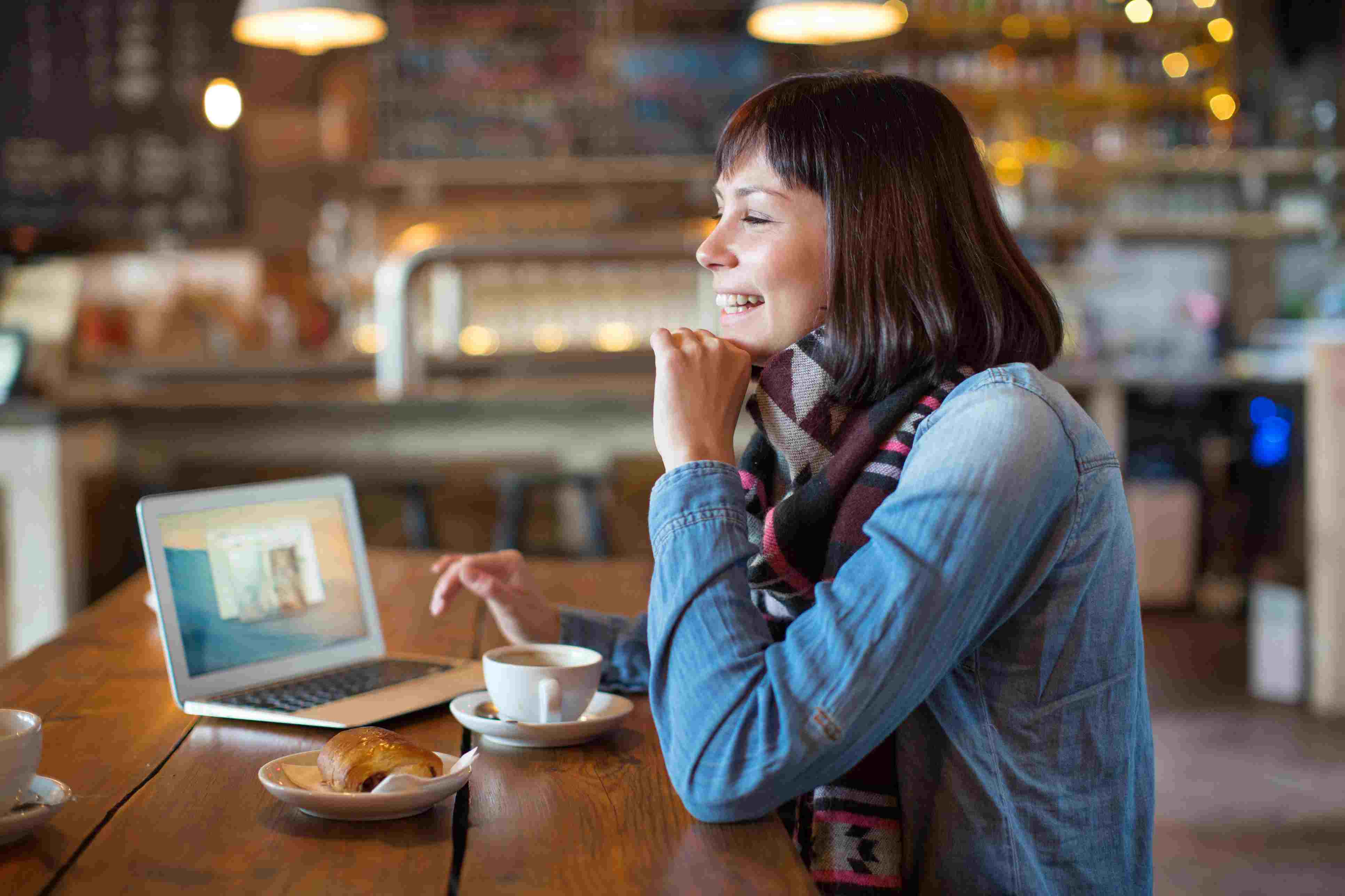 Smiling woman using laptop at coffee shop