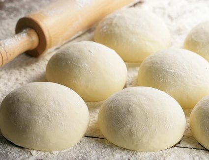 A set of pizza dough balls and a rolling pin