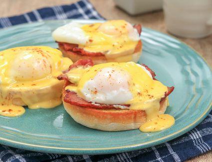 Homemade hollandaise sauce over eggs Benedict