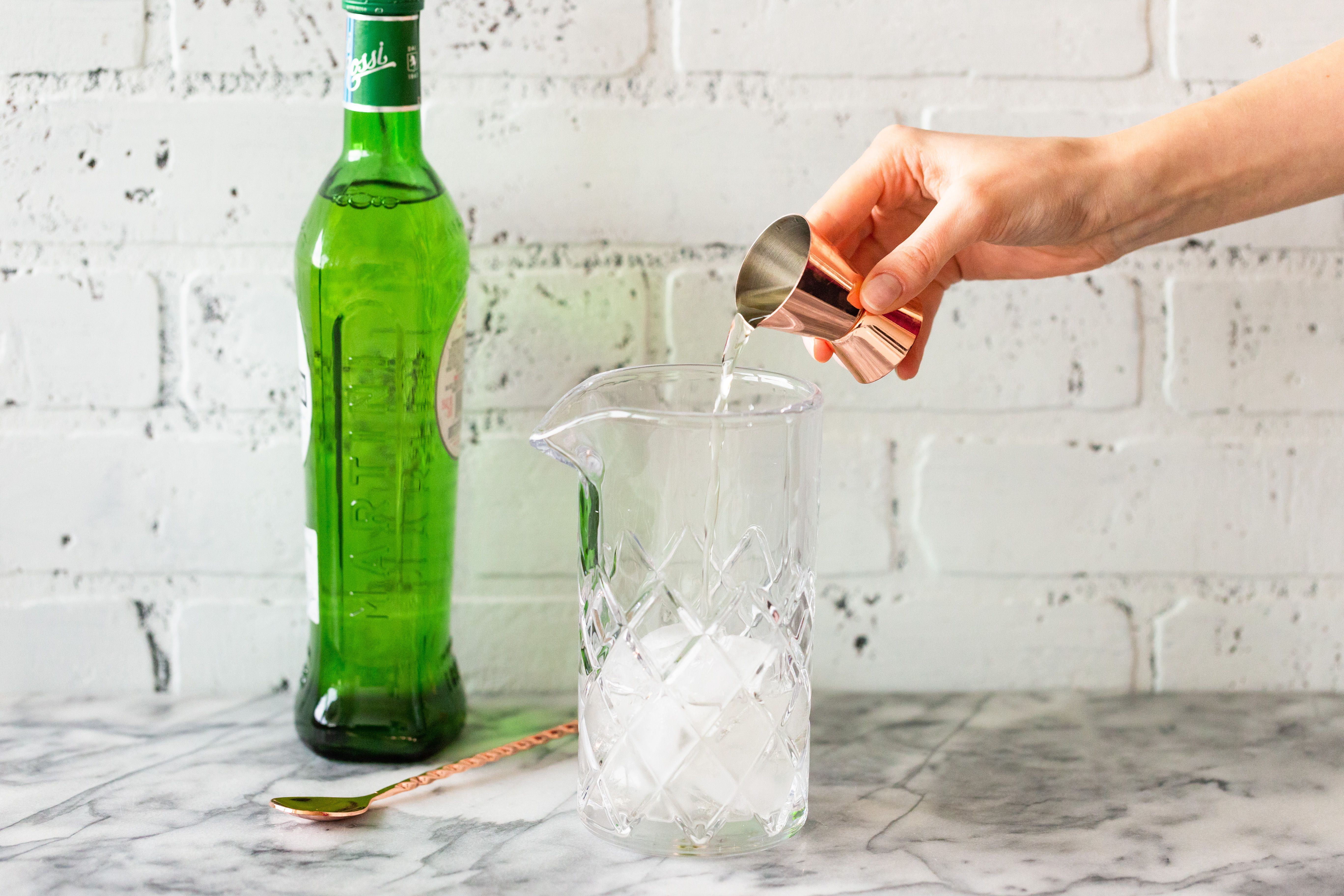 Mixing glass with ice cubes, gin, and dry vermouth.
