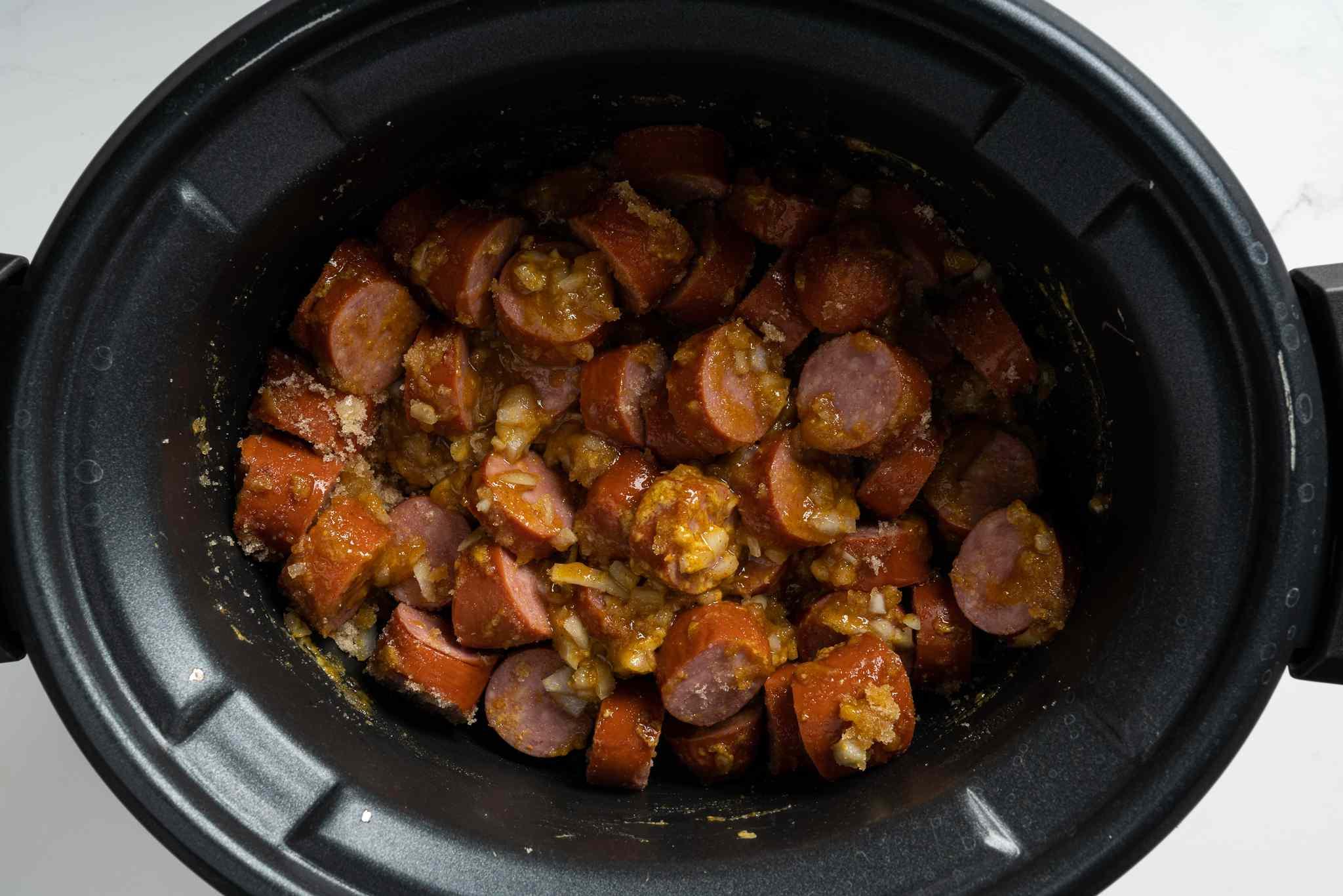 In the crock pot, combine brown sugar, mustard, and onion; add the kielbasa and stir well