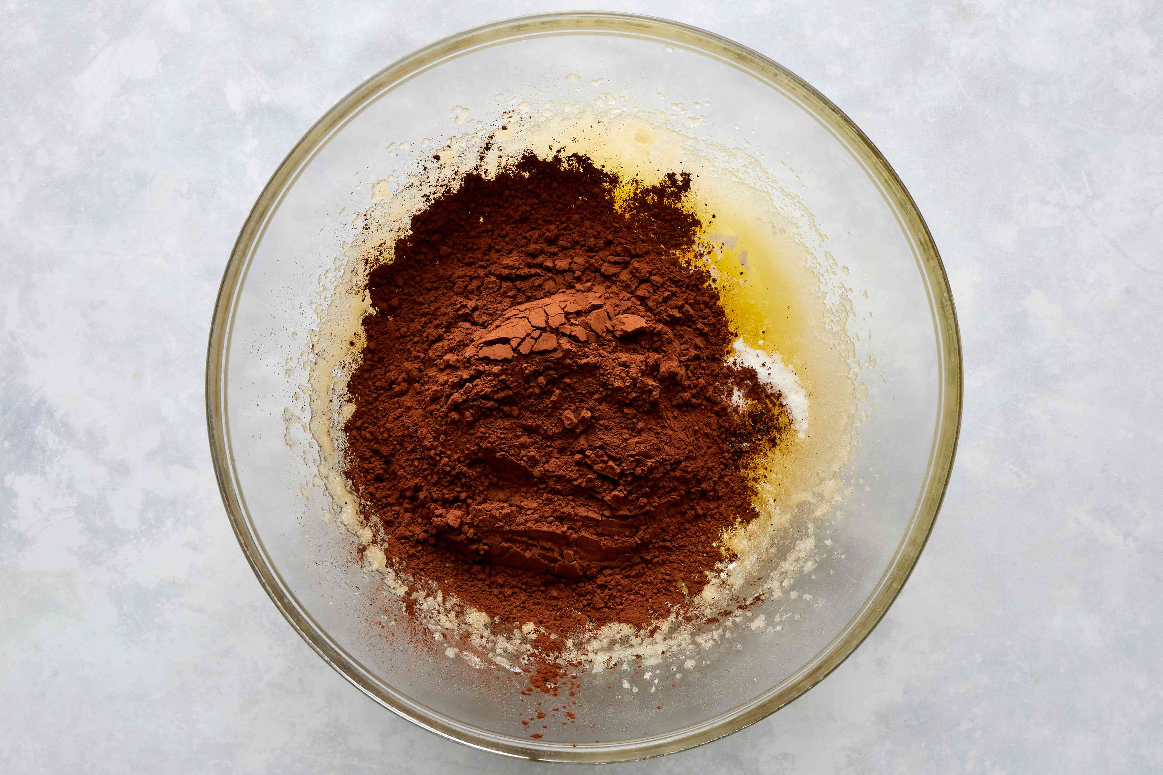 salt, vanilla extract, baking soda, baking powder, and cocoa powder on top of the butter and sugar mixture in a large glass bowl
