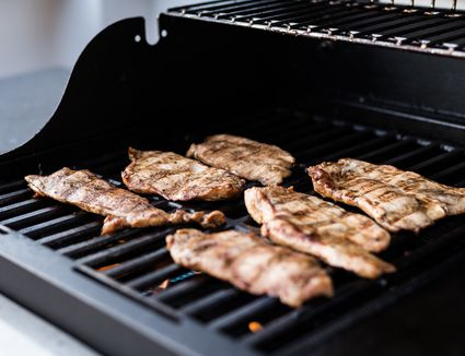Grilling marinated turkey breast on a gas barbecue