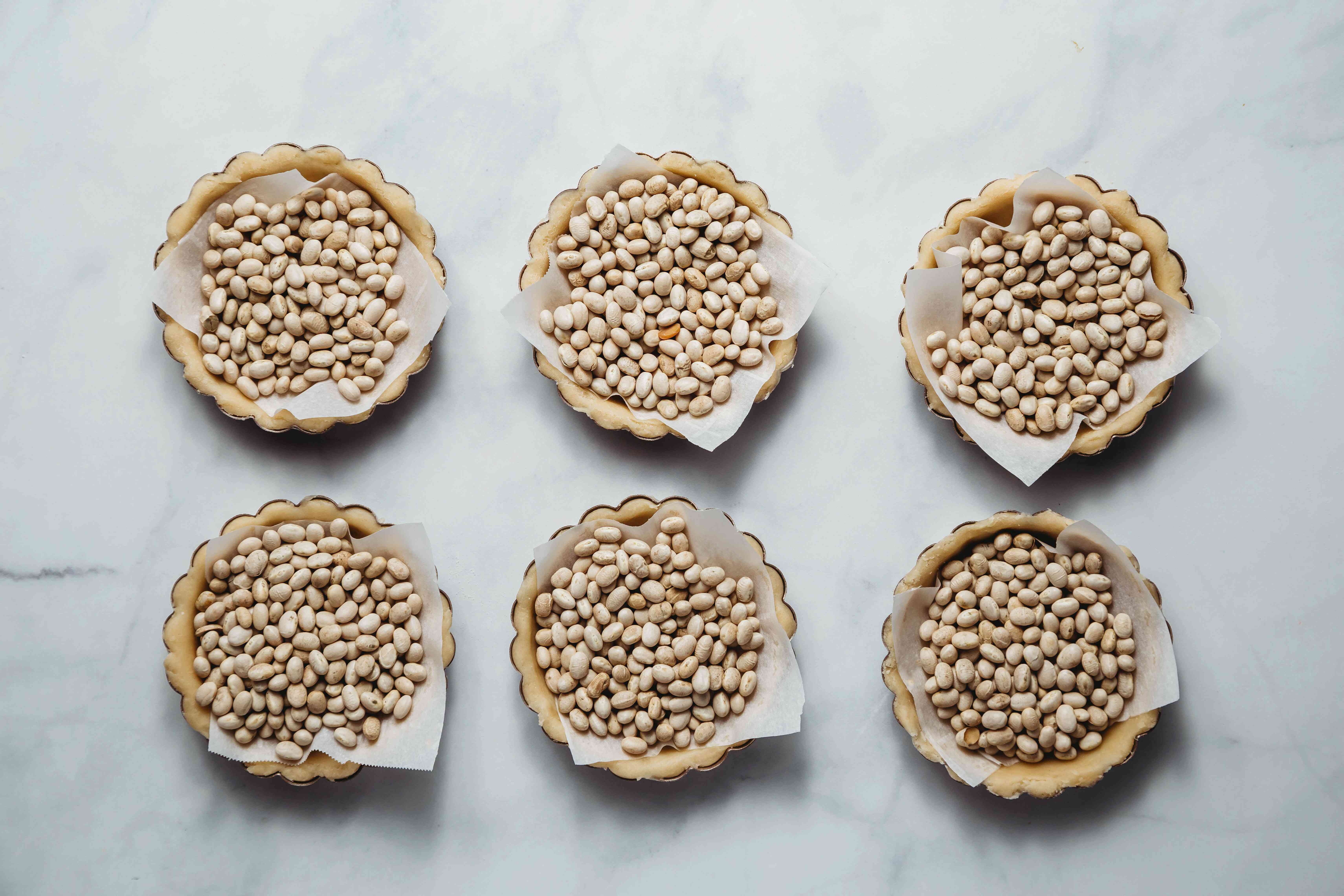 Line the shells with parchment paper and fill with uncooked beans