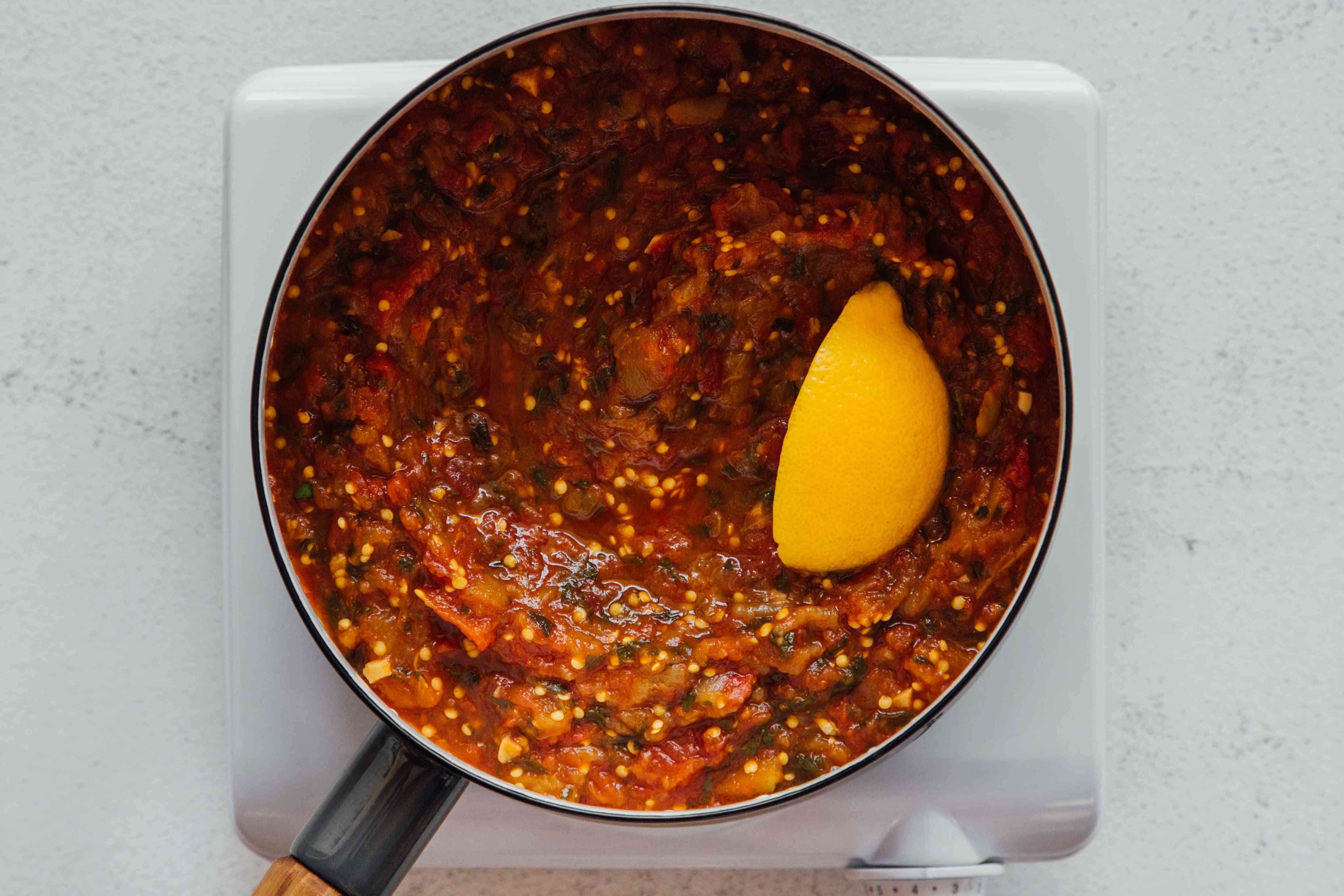 Tomato and eggplant mixture in a pan with a lemon wedge
