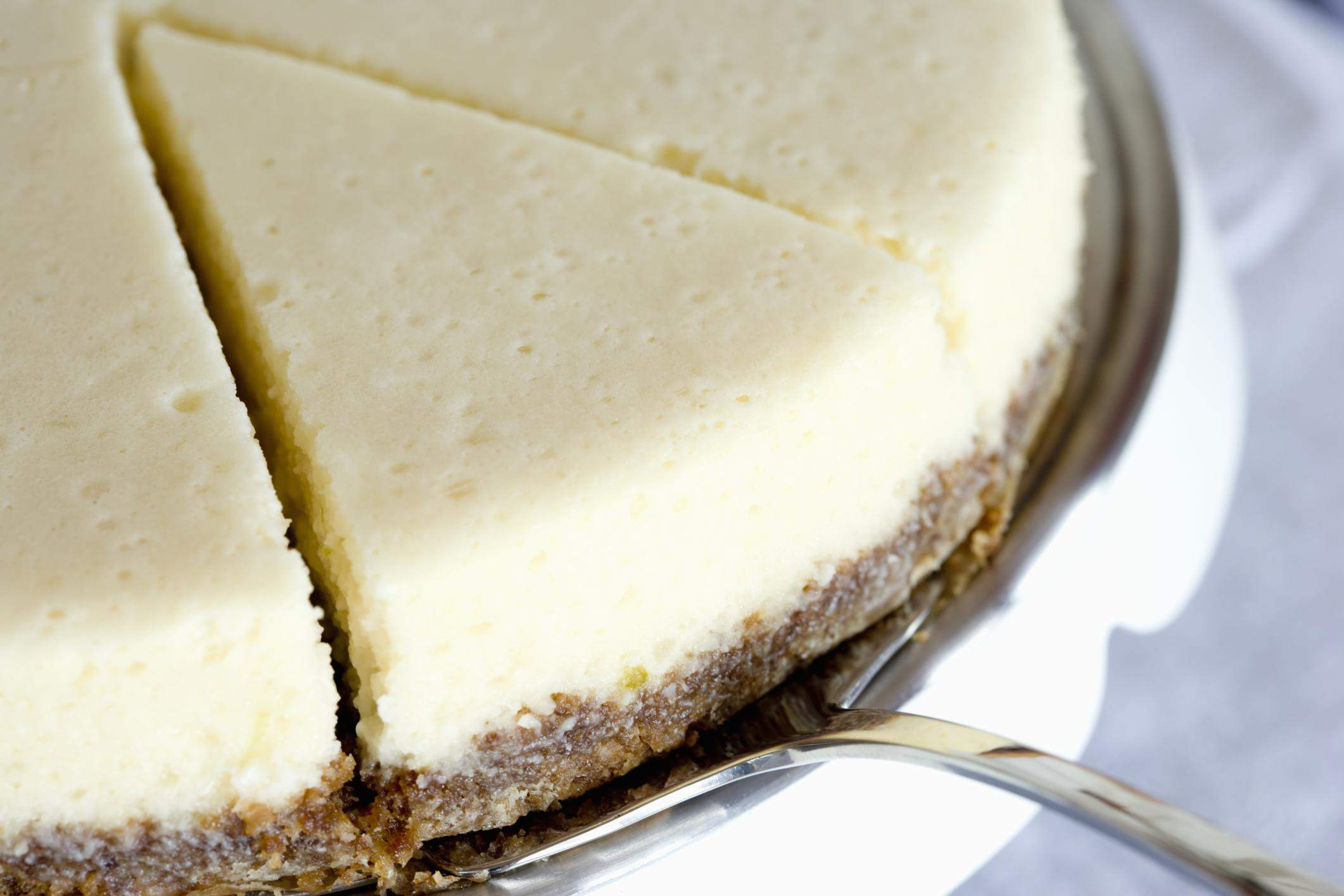 Slice of cheesecake on silver platter, close up