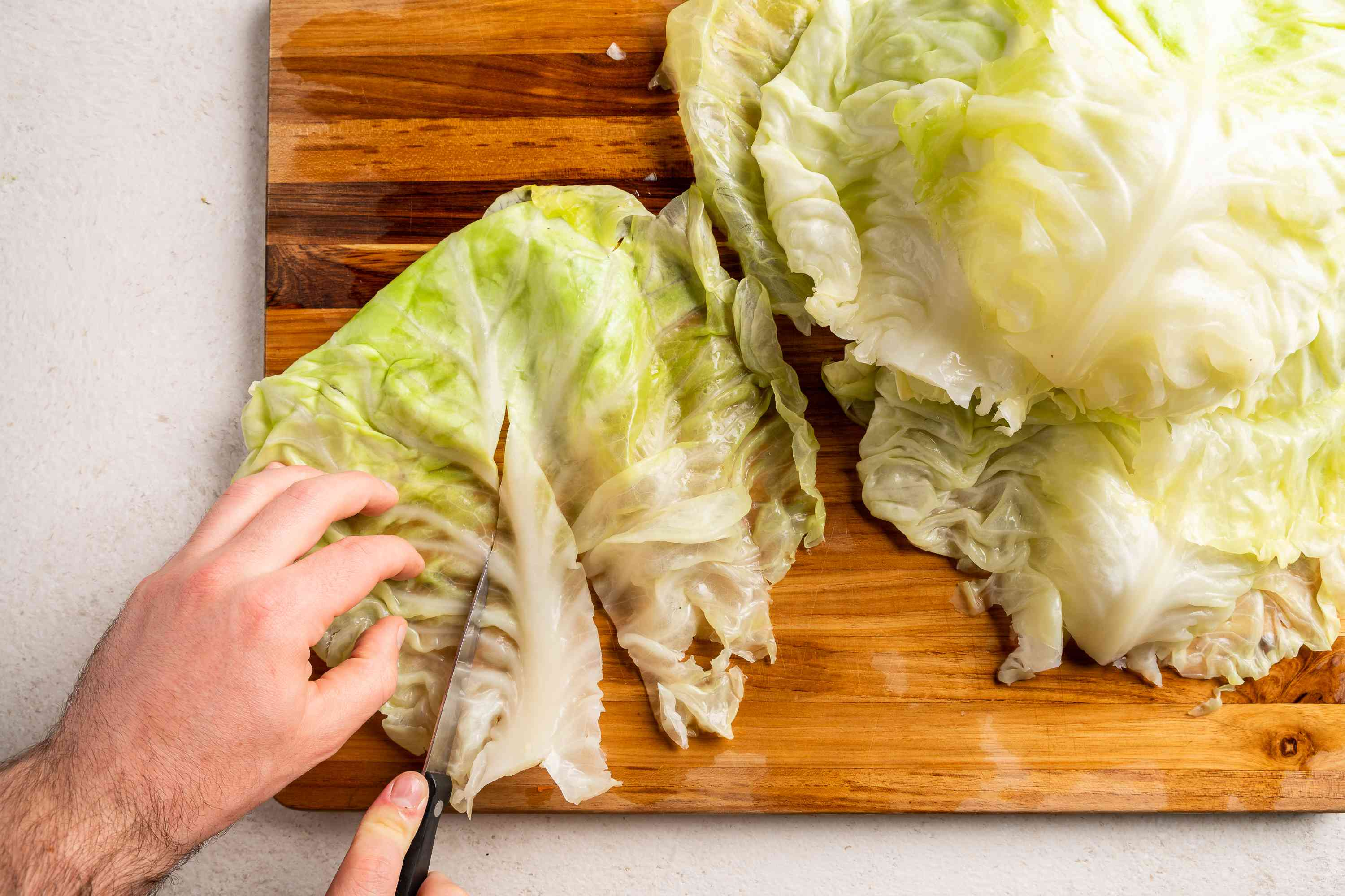 cut off the thick white portion in the middle of each cabbage leaf