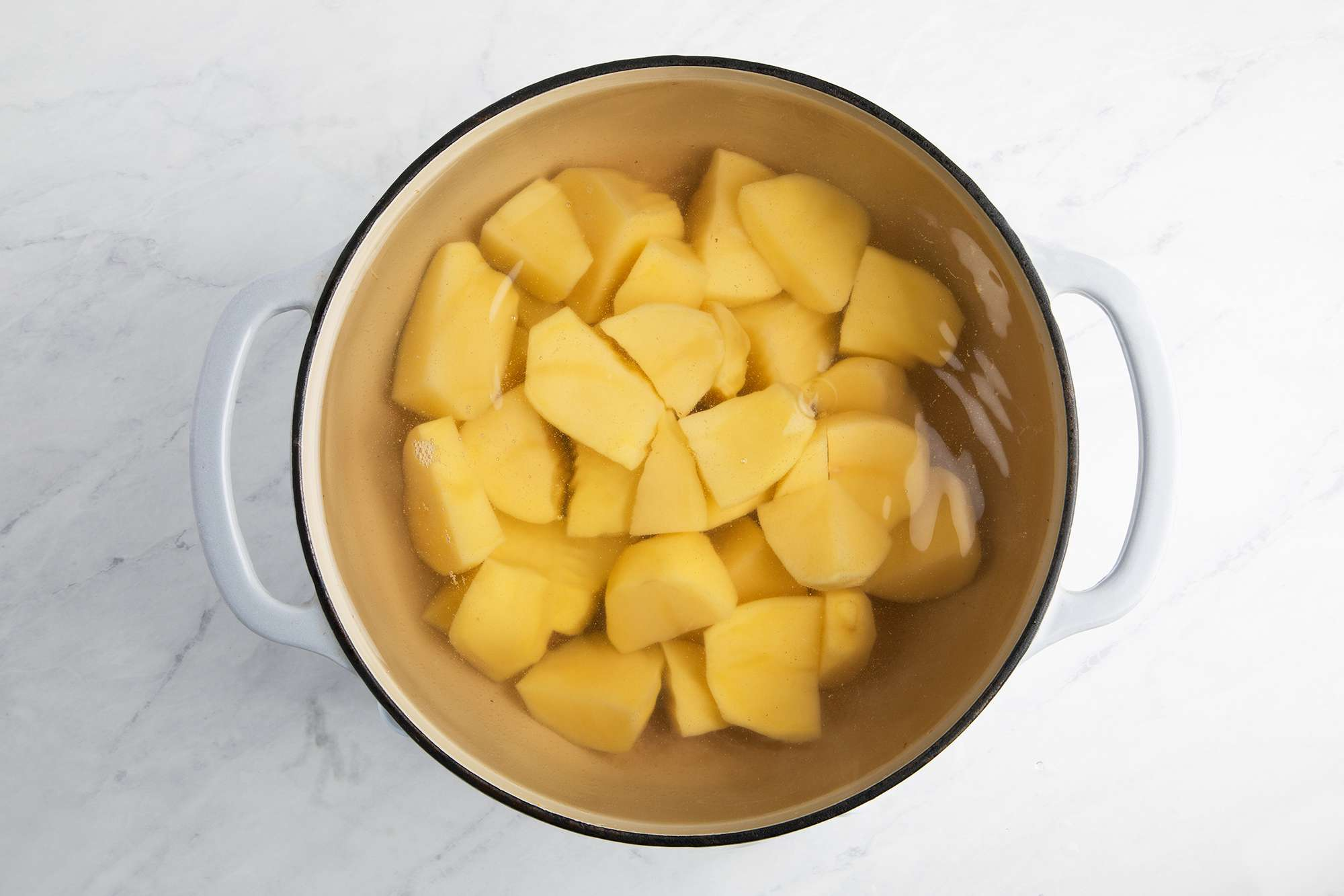 peeled and cut potatoes in a pot of water
