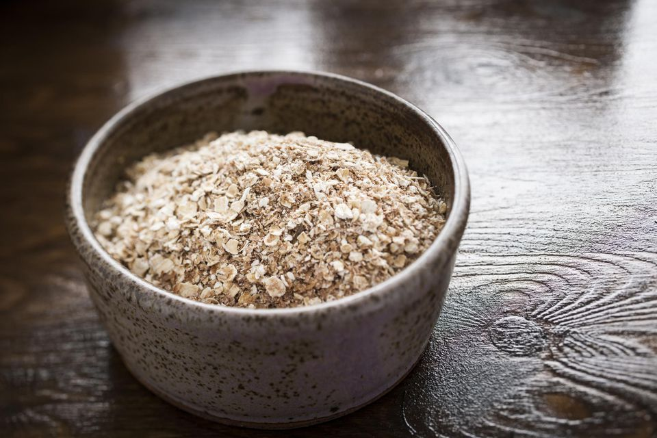 A rustic bowl of uncooked porridge oats (oatmeal)