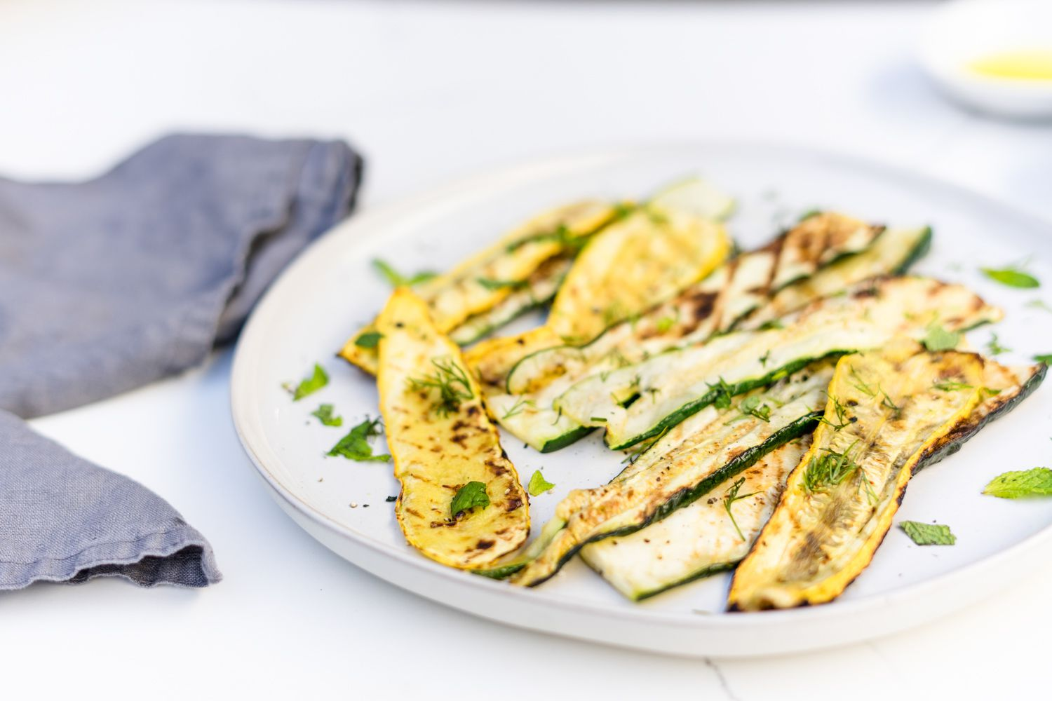 Grilled zucchini and squash on a white dinner plate