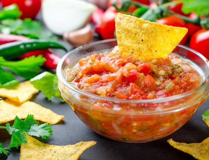 a yellow tortilla chip in a bowl of red salsa
