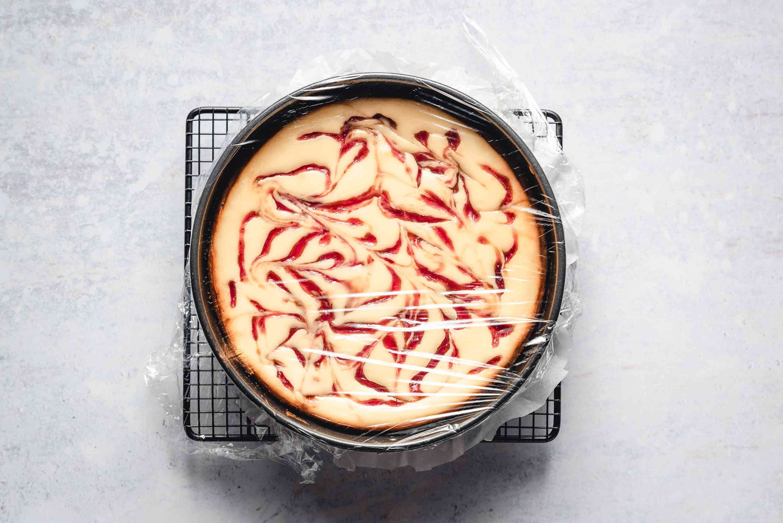 raspberry swirl cheesecake covered with plastic wrap