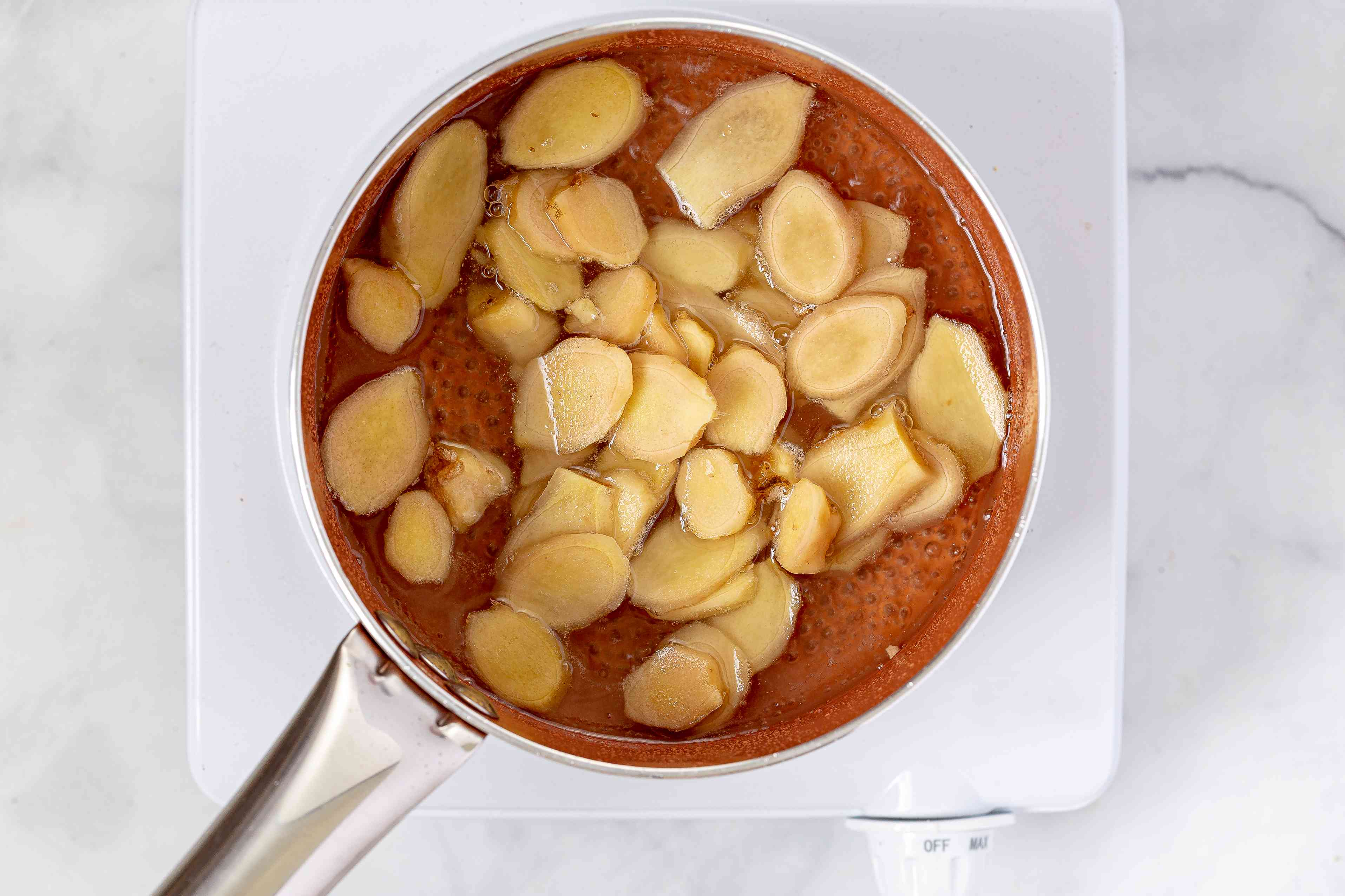 Slices of ginger simmering in simple syrup in a saucepan