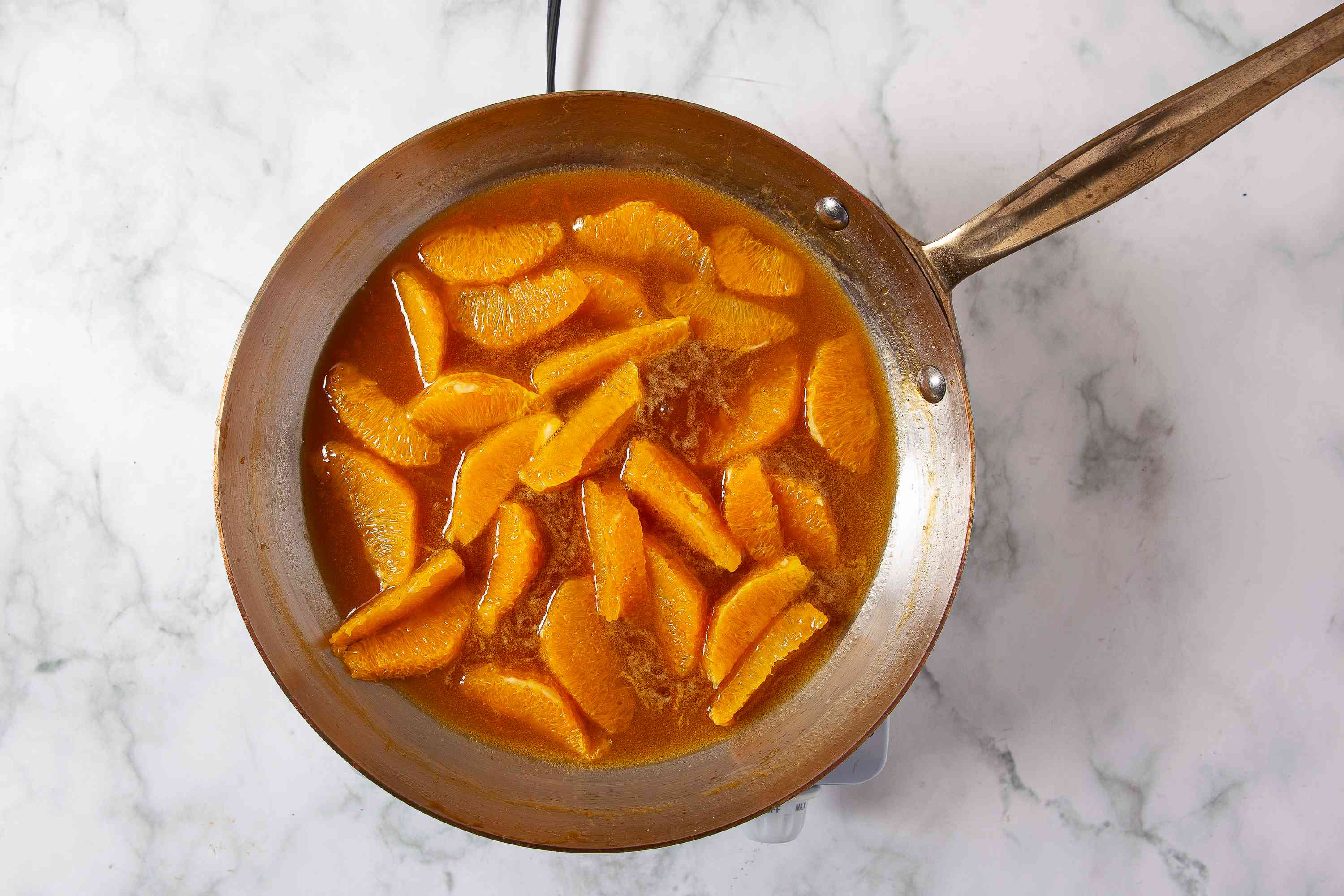 orange sections added to the sauce in the pan
