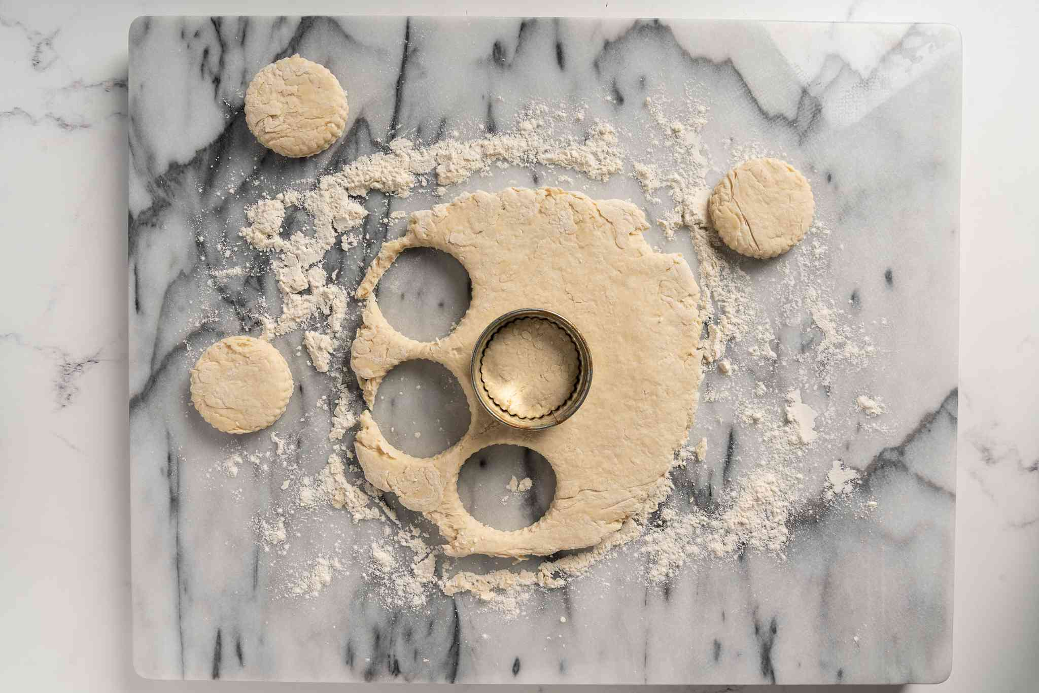 biscuits cut out of dough with a biscuit cutter