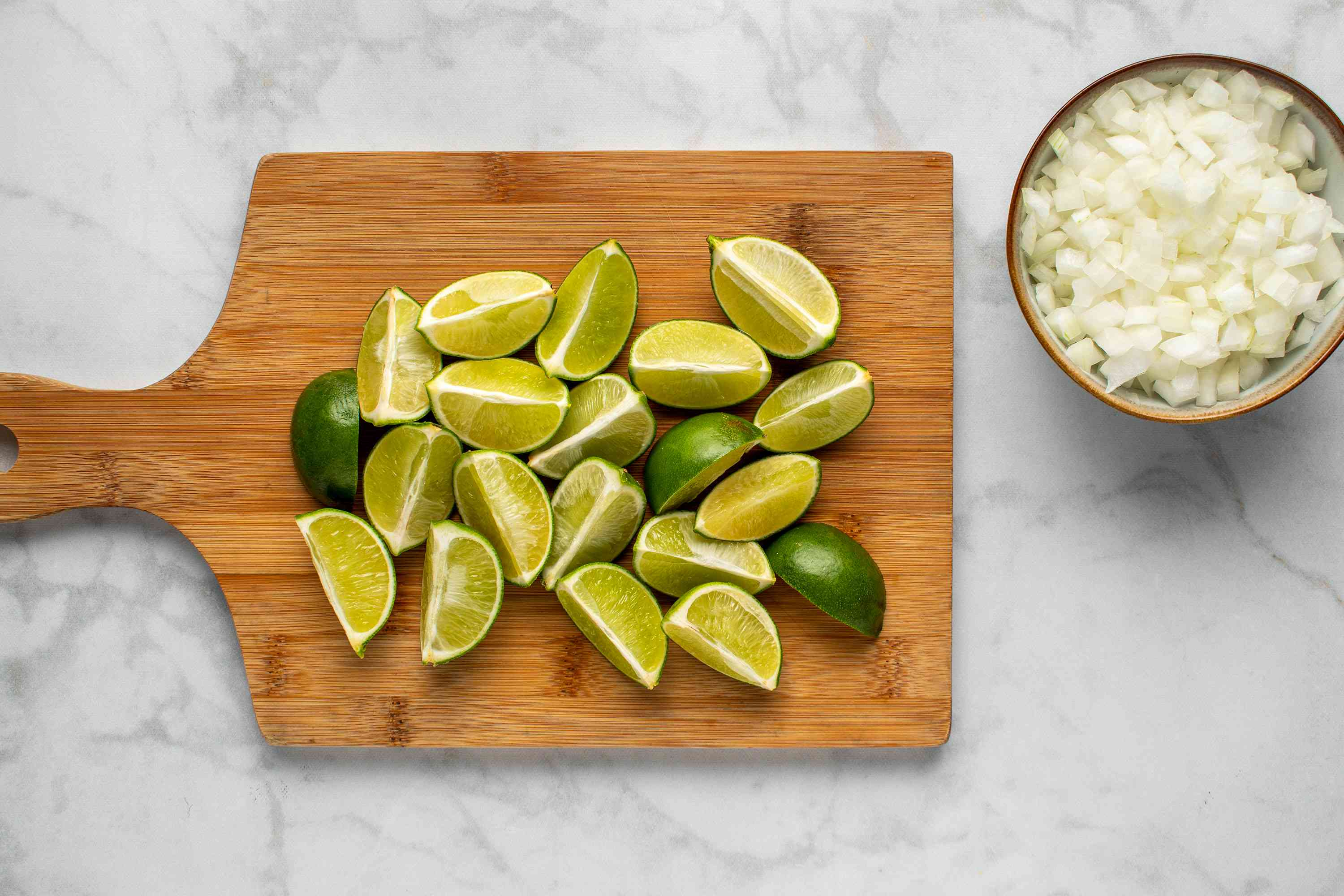 lime wedges on a cutting board and diced onions in a bowl