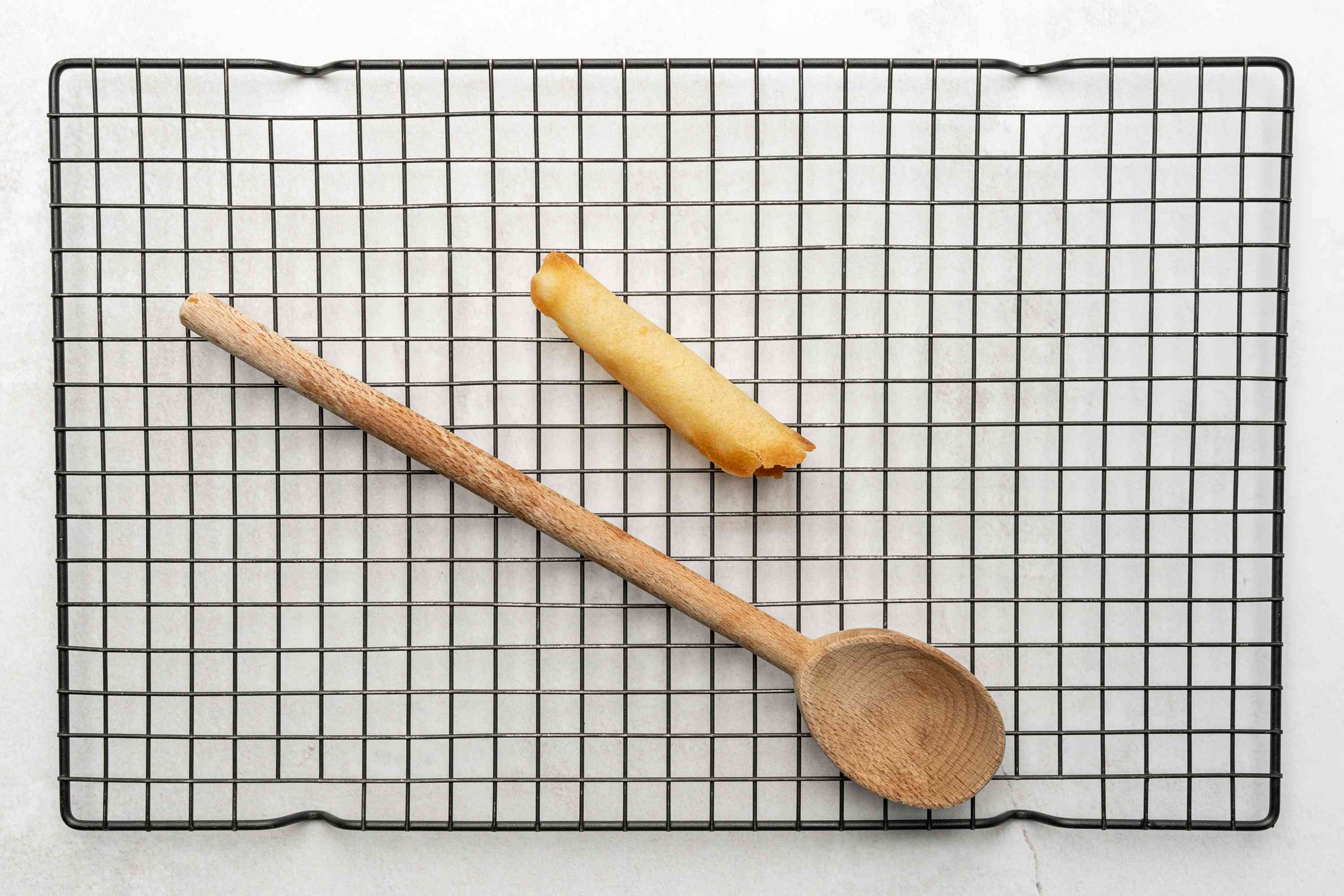 pirouette cookie on a cooling rack, wooden spoon