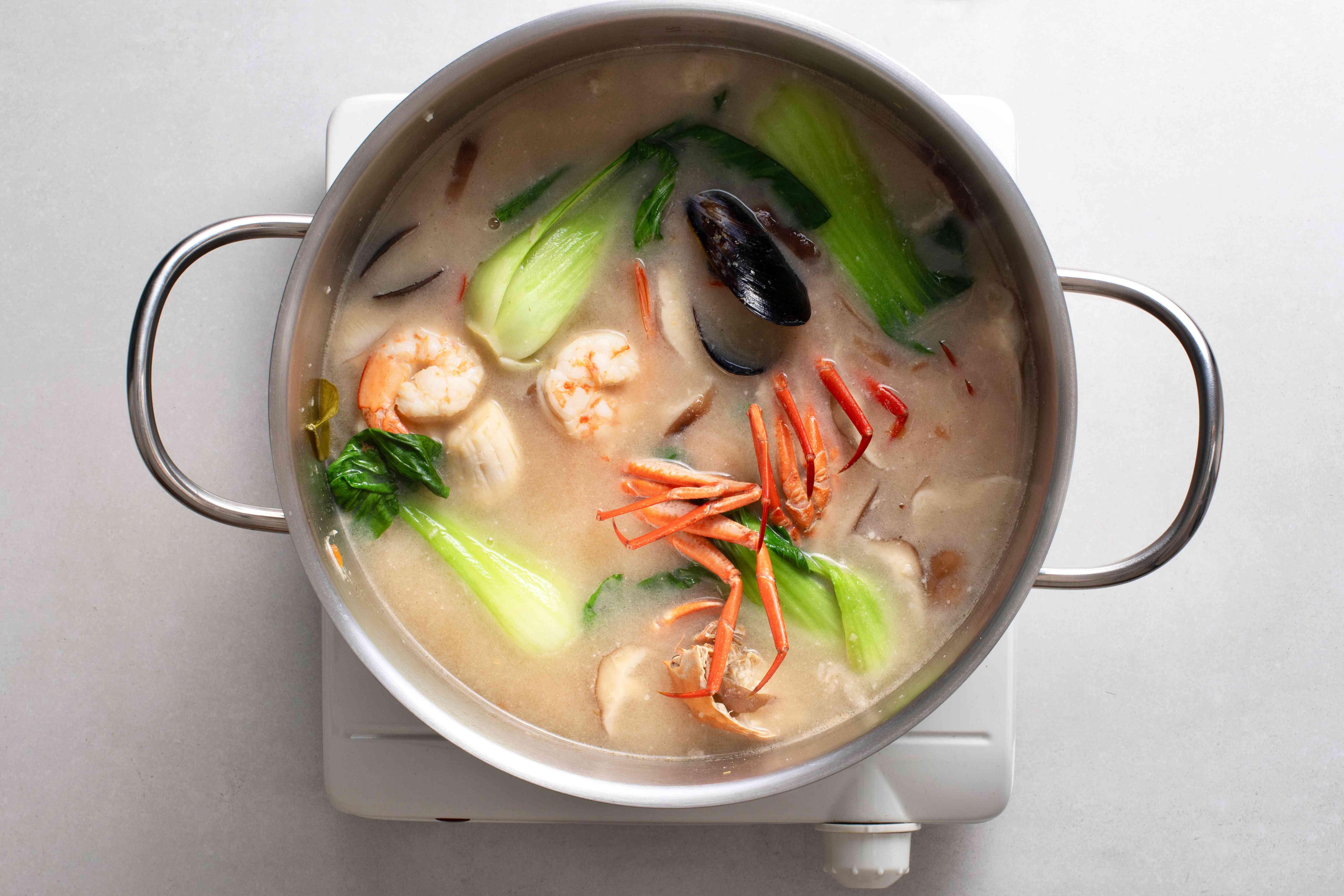 A pot of coconut milk broth with vegetables and cooked seafood simmering