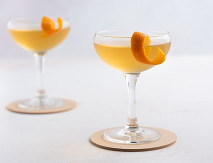 Two glasses of fancy whiskey cocktail, with orange twist