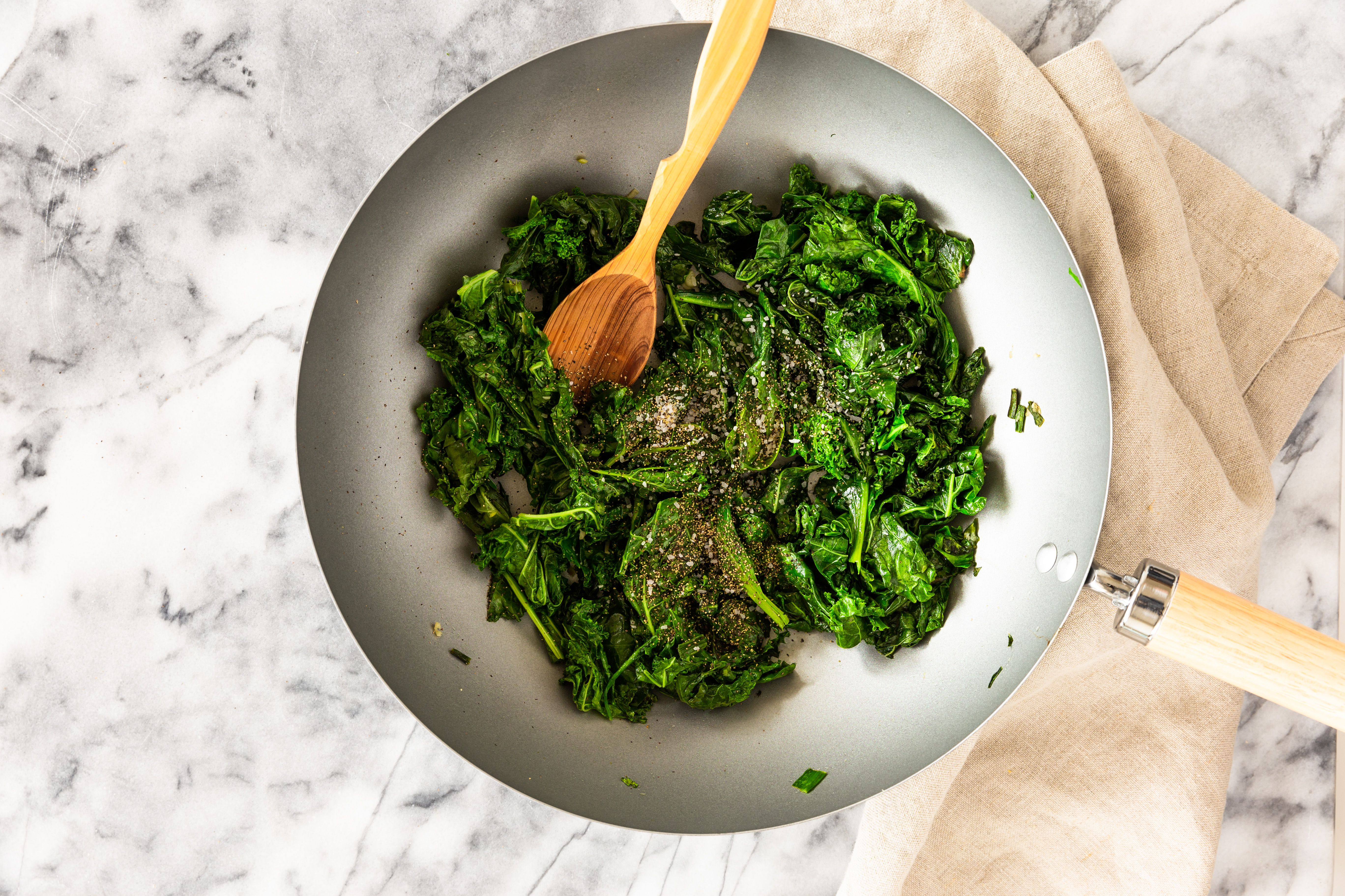 Season greens with salt and pepper