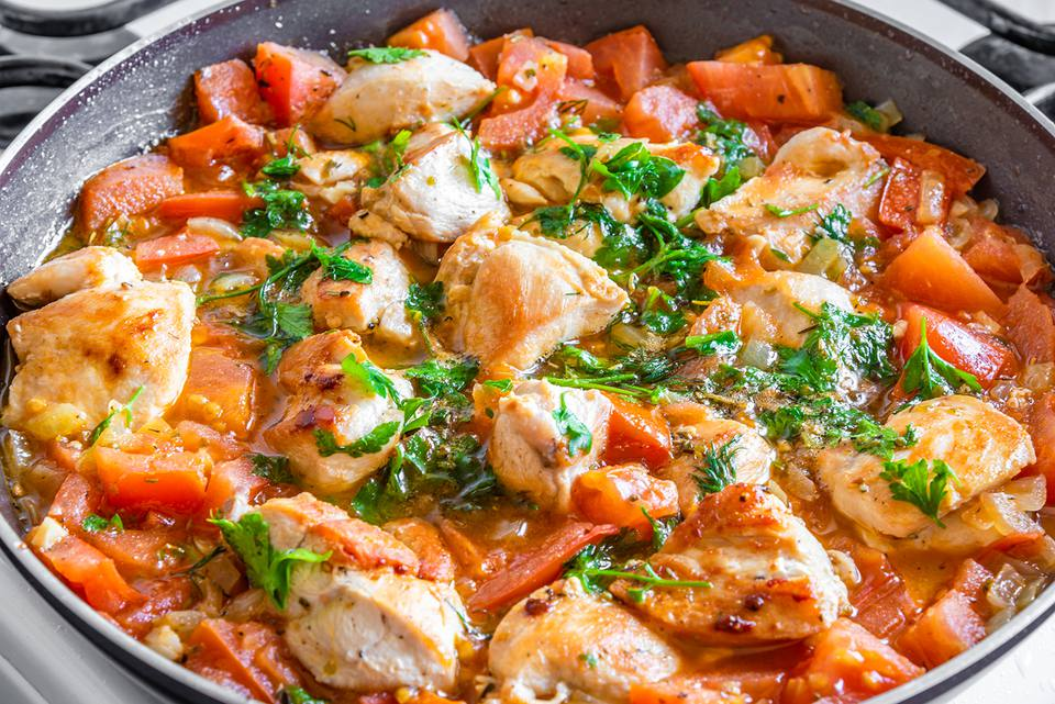 Chicken cacciatore is cooked in a frying pan, chicken stew with tomatoes and red pepper