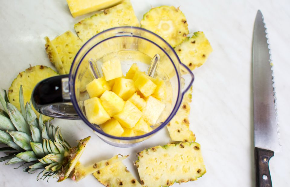 Sliced pineapple in a blender on a marble countertop.