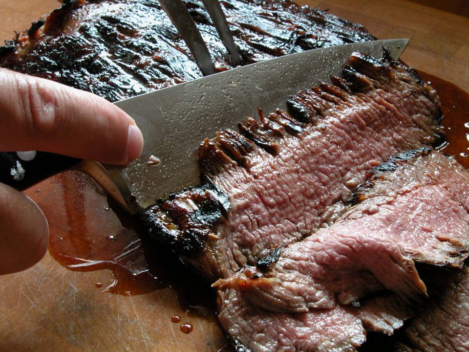 Knife carving a piece of grilled flank stake