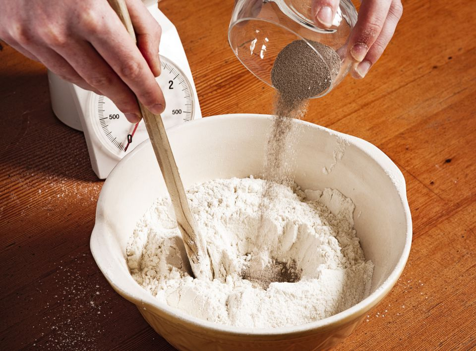 A person pouring yeast into a bowl.