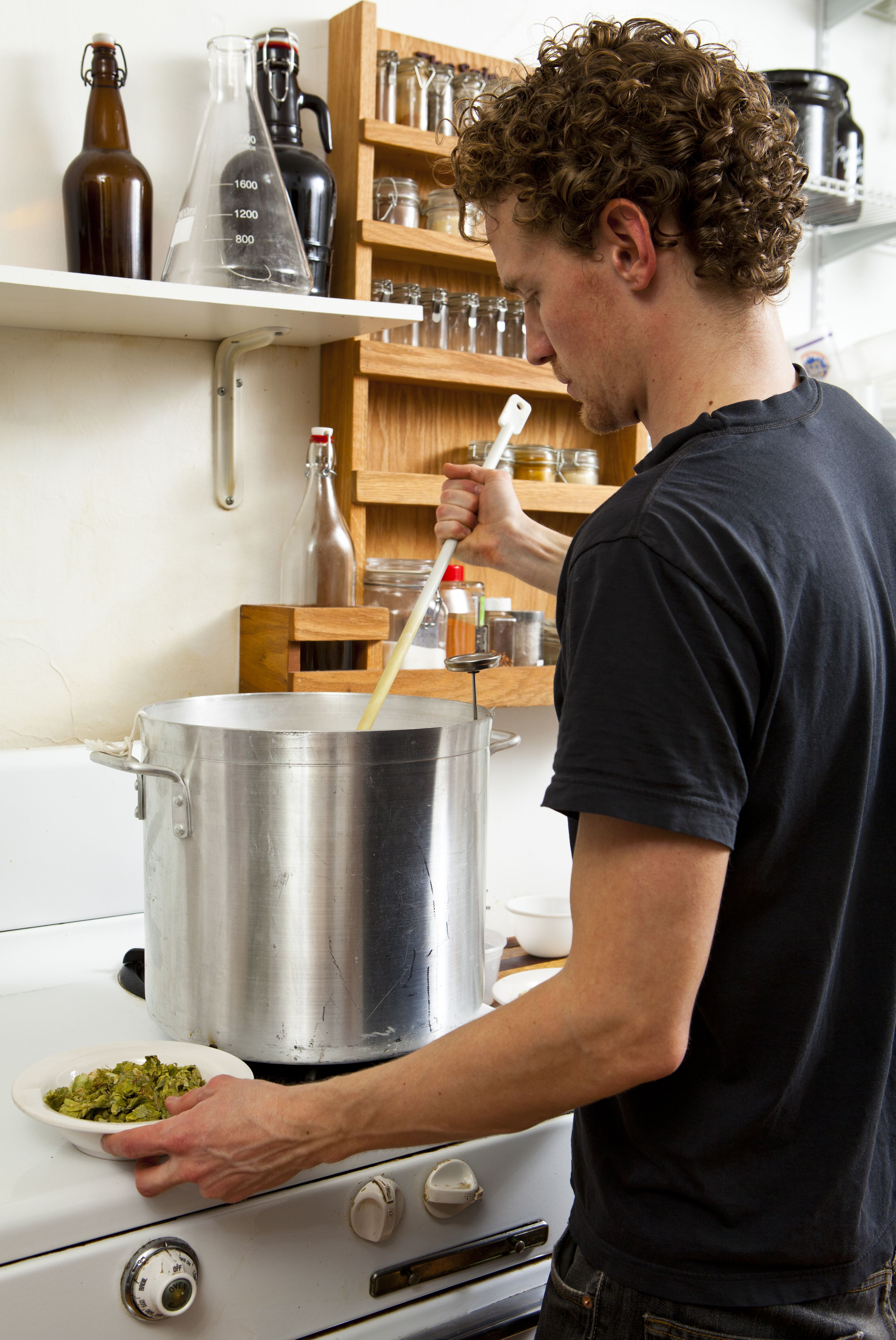 Home beer brewer adding hops to recipe