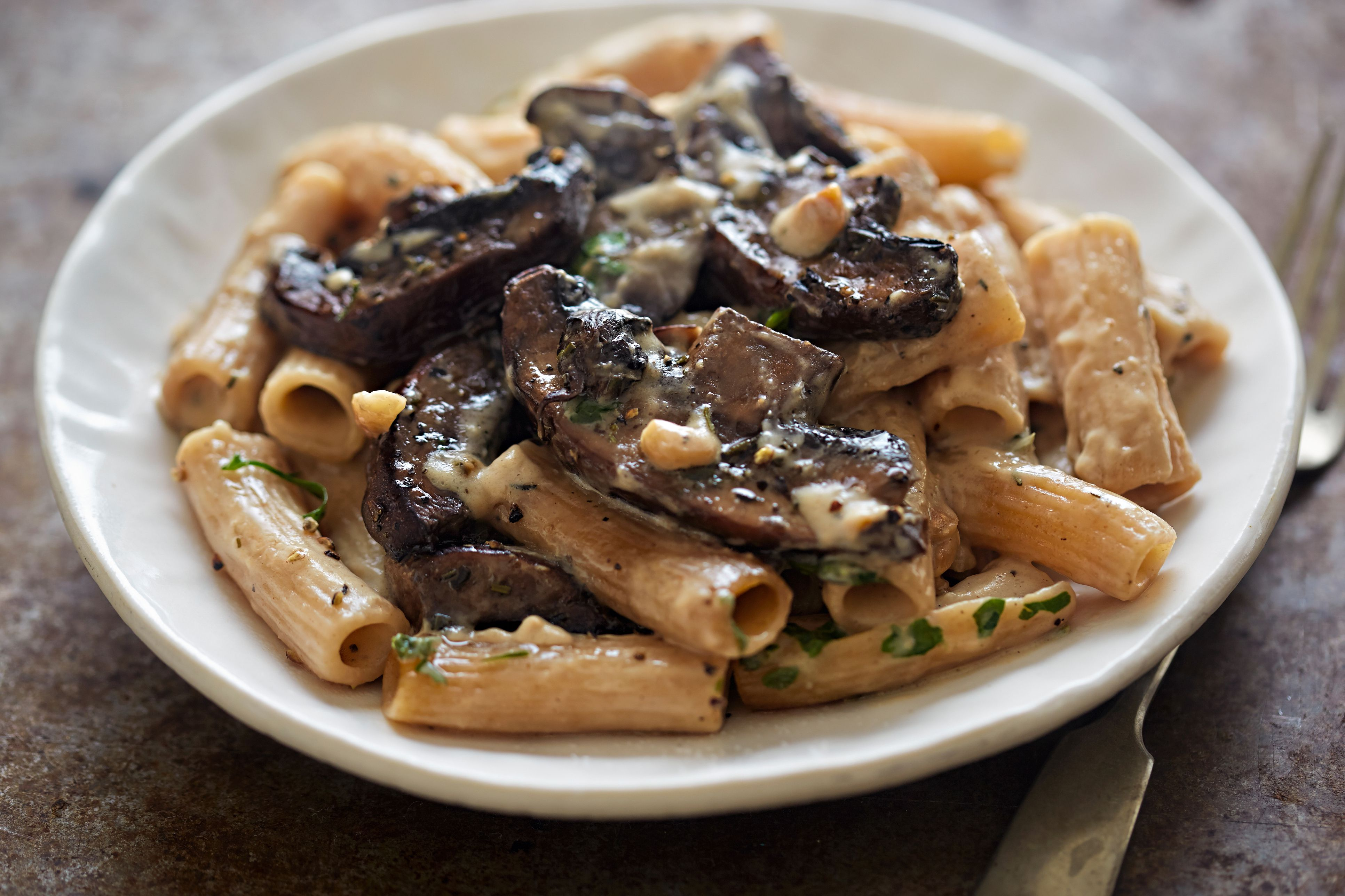 Pasta rigatoni with mushroom sauce and nuts