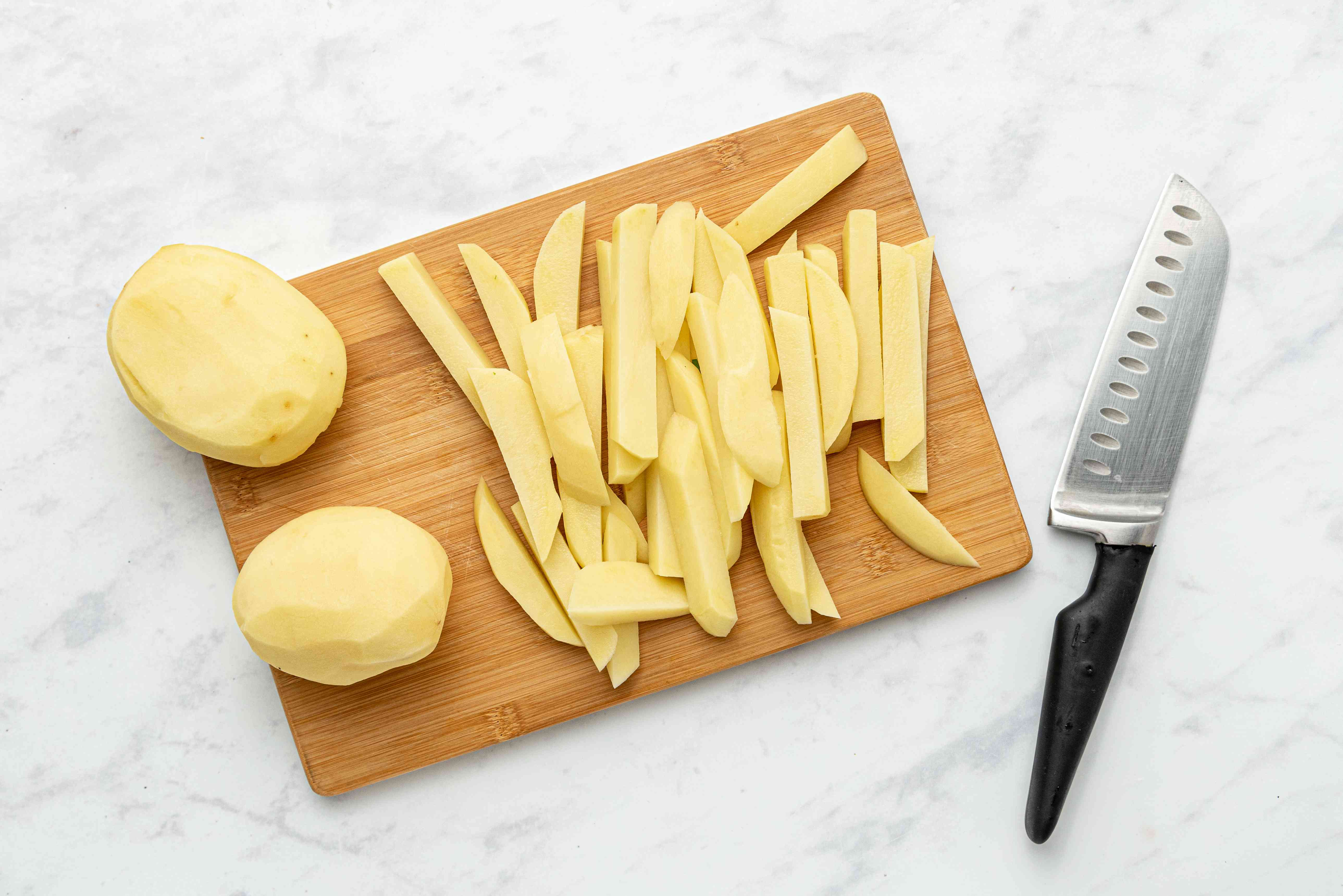 peeled potatoes cut into fries on a cutting board