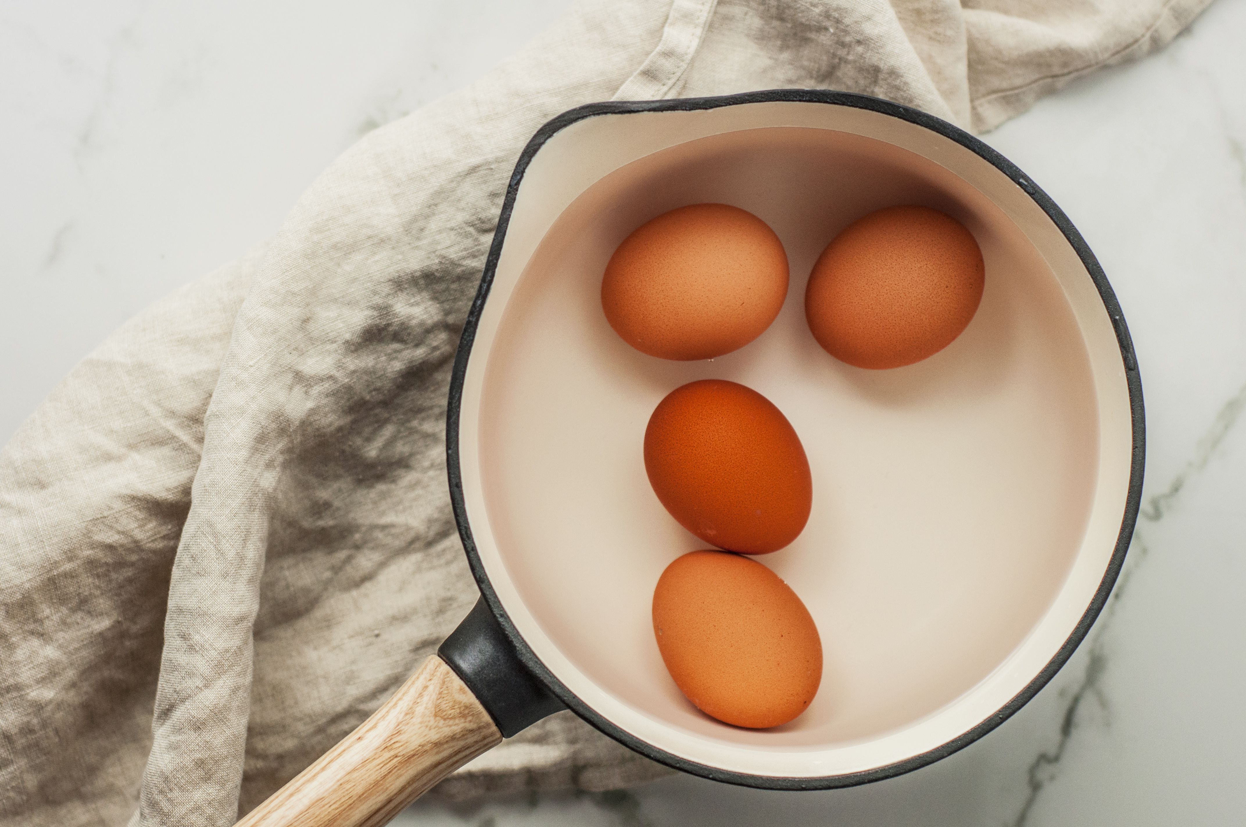 Hard-boiled eggs placed in a pot of water