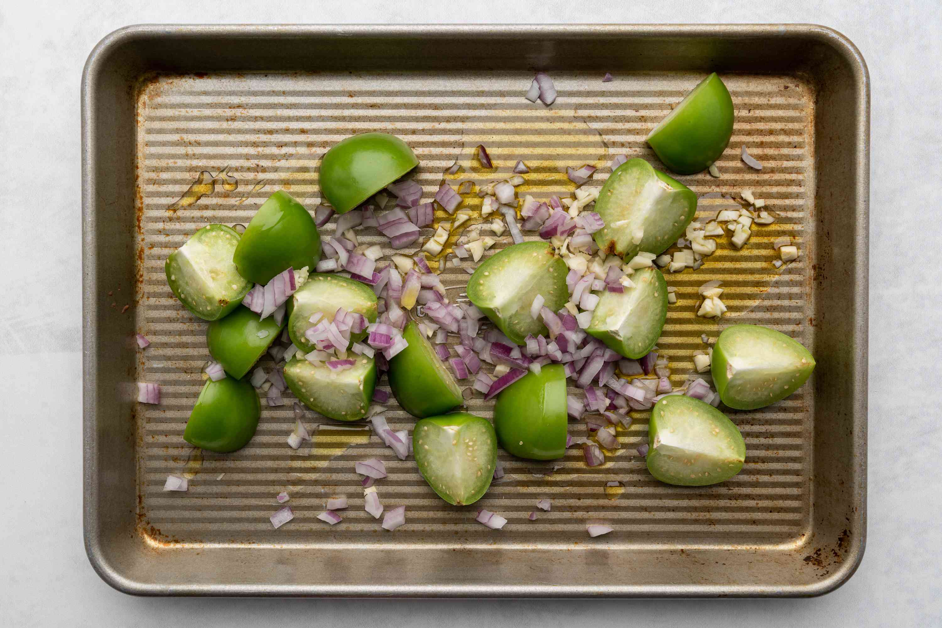 tomatillos, onions, and garlic coated with olive oil on a sheet pan