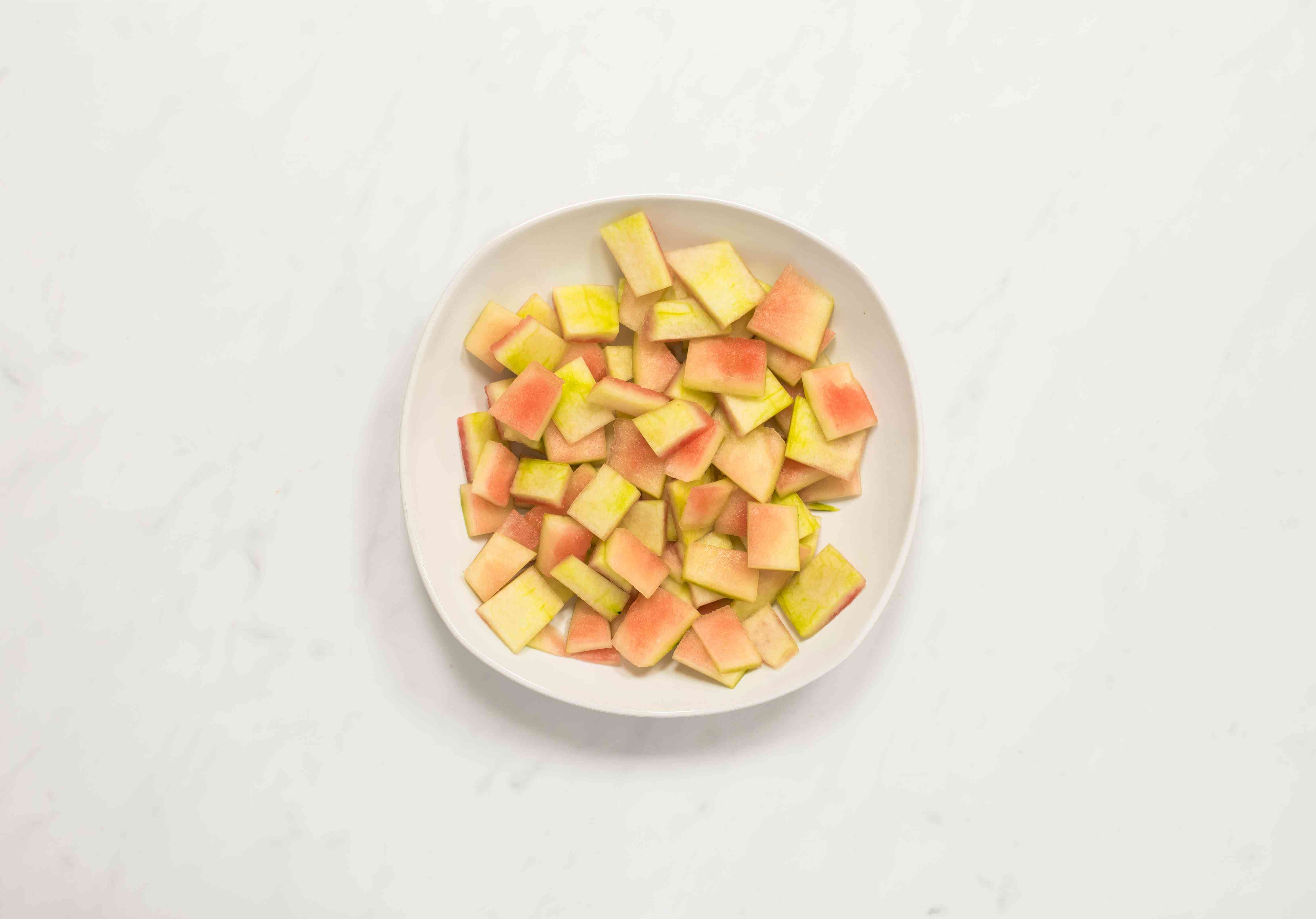 Trimmed and cut watermelon rind in a bowl