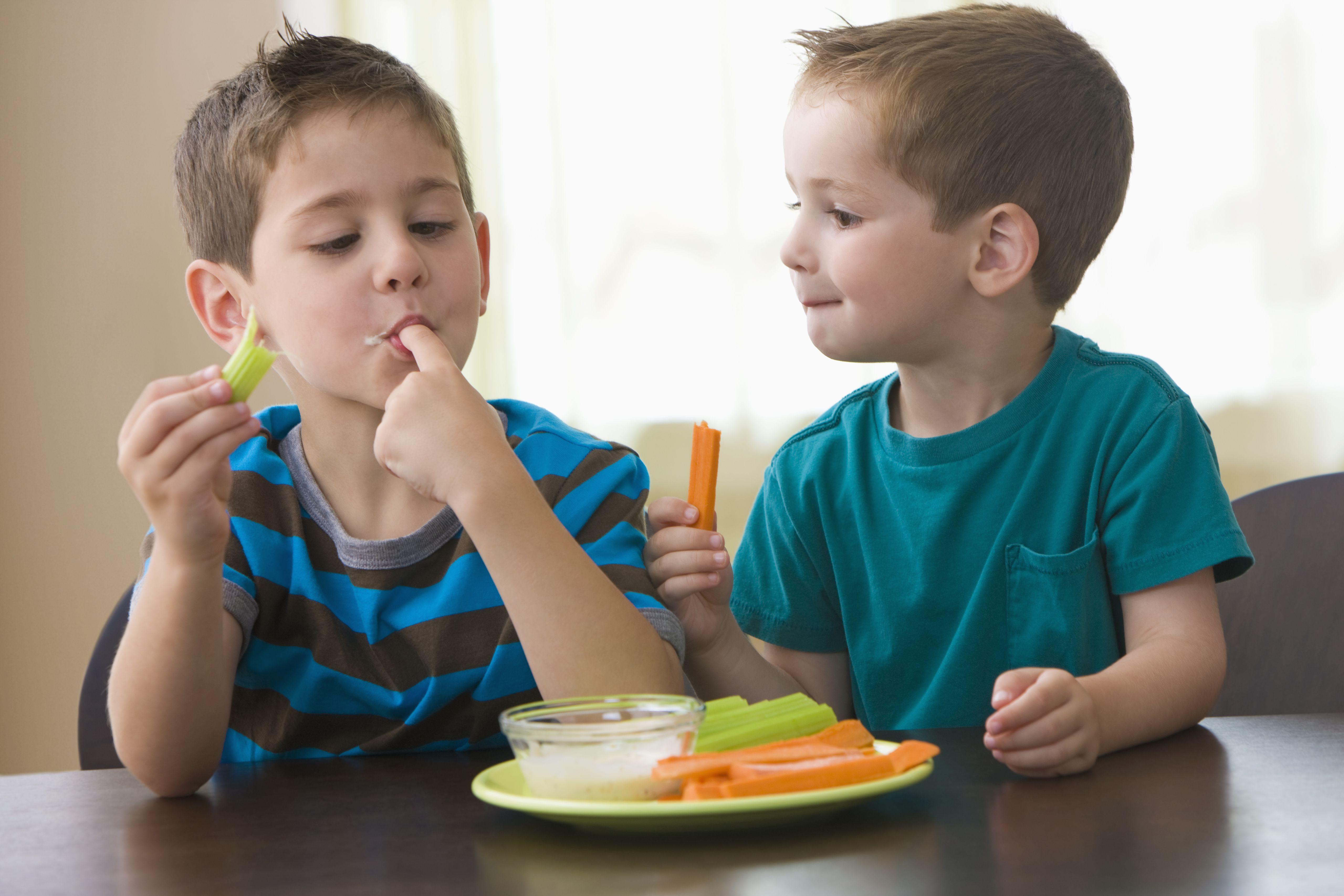 Two boys dipping veggies