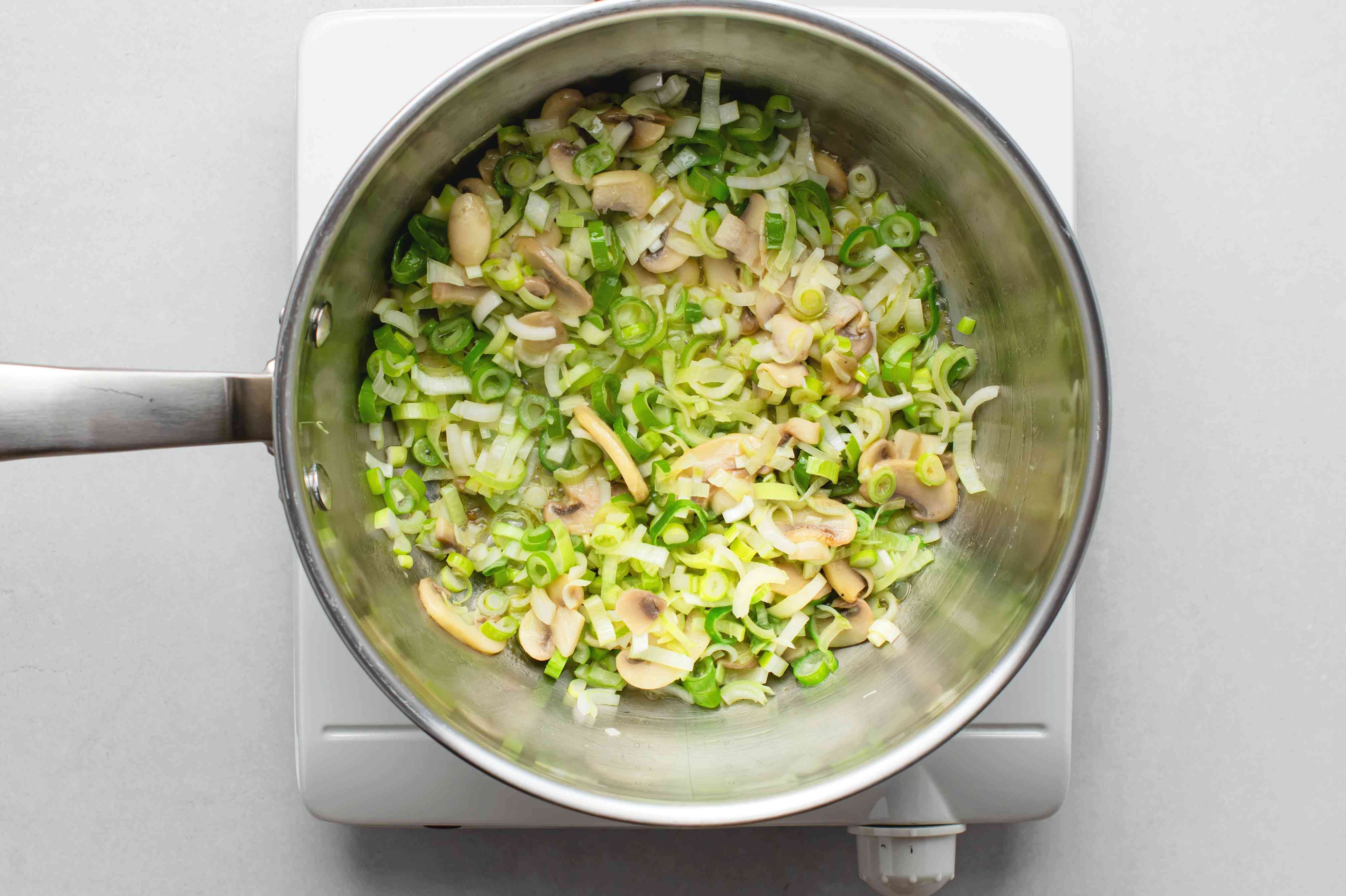green onions and mushrooms in a saucepan