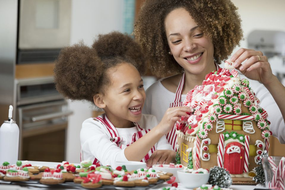 mom and daughter making gingerbread house