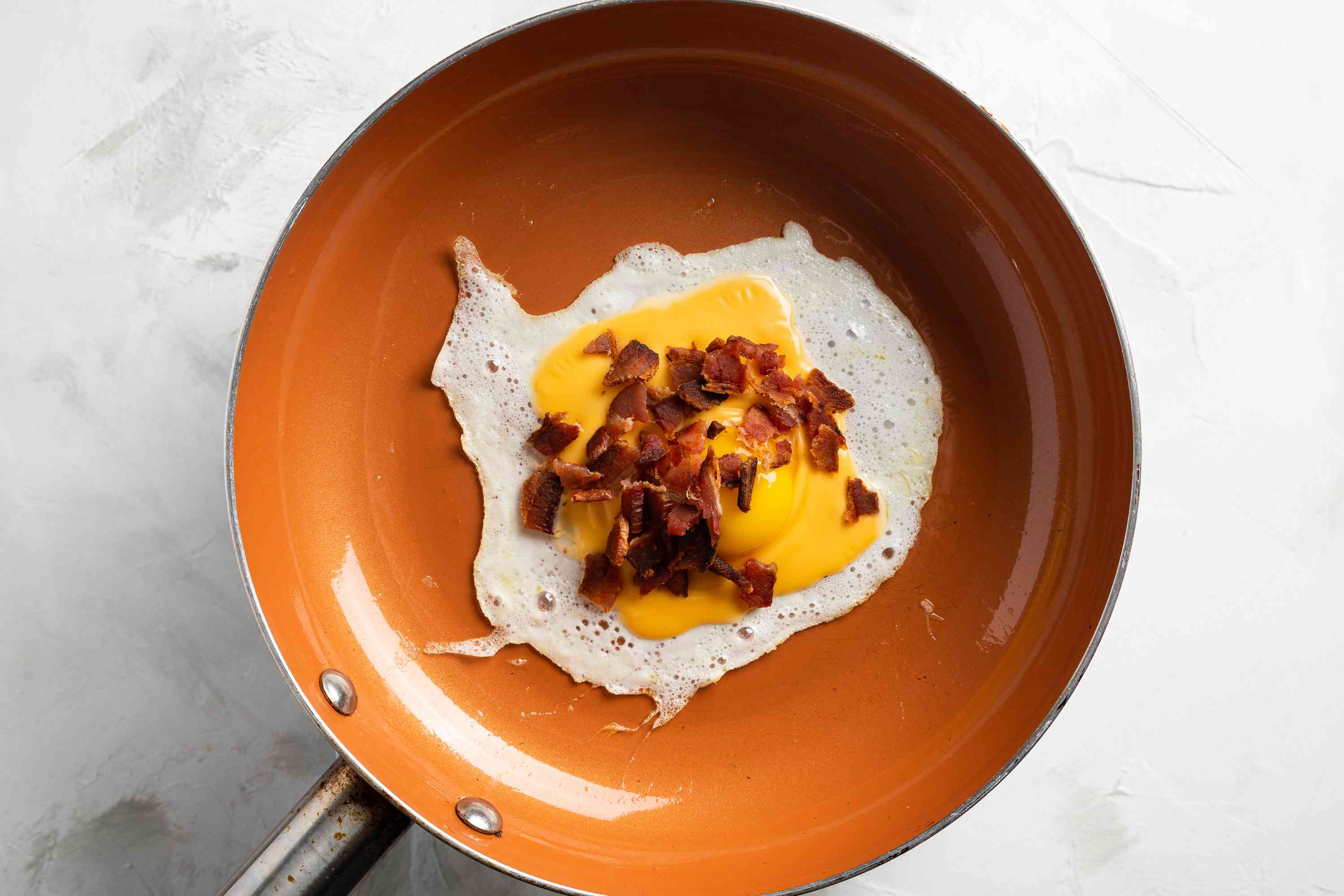 egg yolk and bacon crumbles added to pan with egg white and cheese