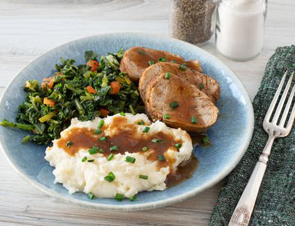 instant pot pork tenderloin on a plate with potatoes and kale