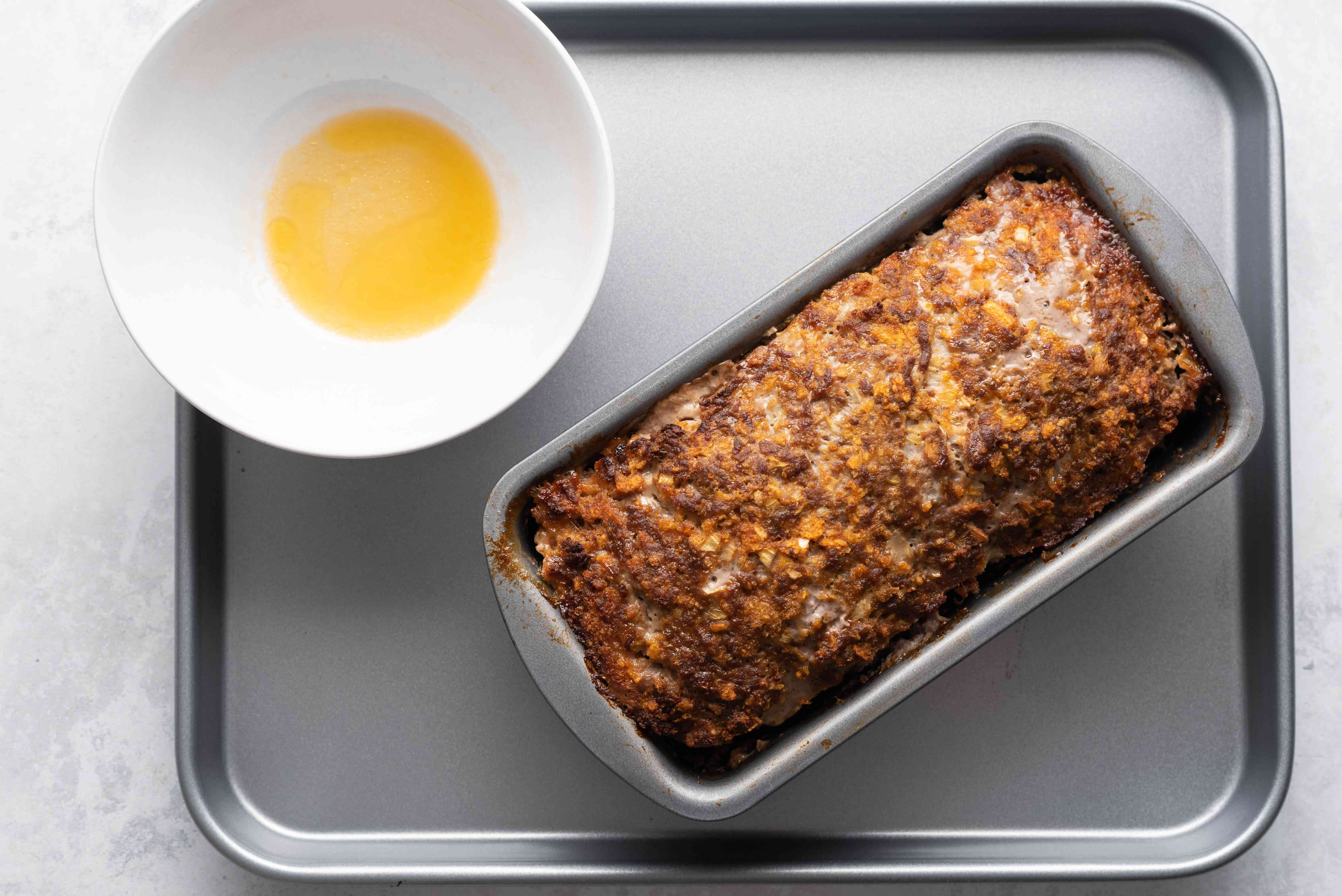 Cooked meatloaf in loaf pan with extra fat in bowl