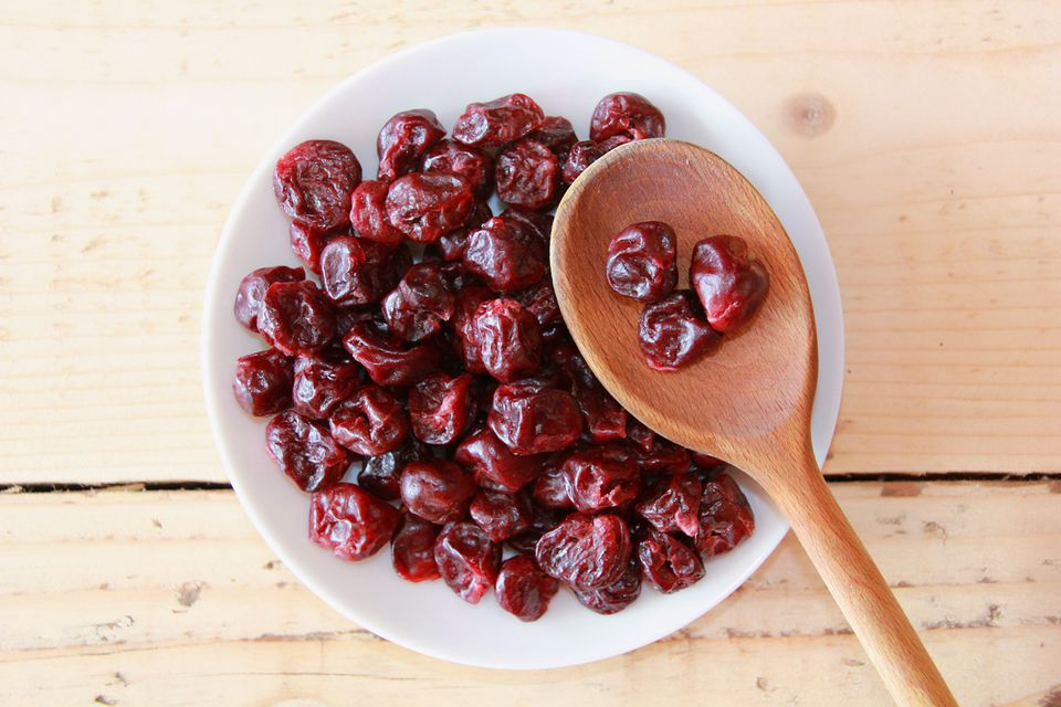 Dried cherries in a bowl with a wooden spoon