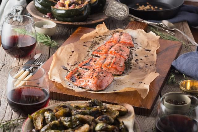 Dinner table spread including salmon baked in parchment paper