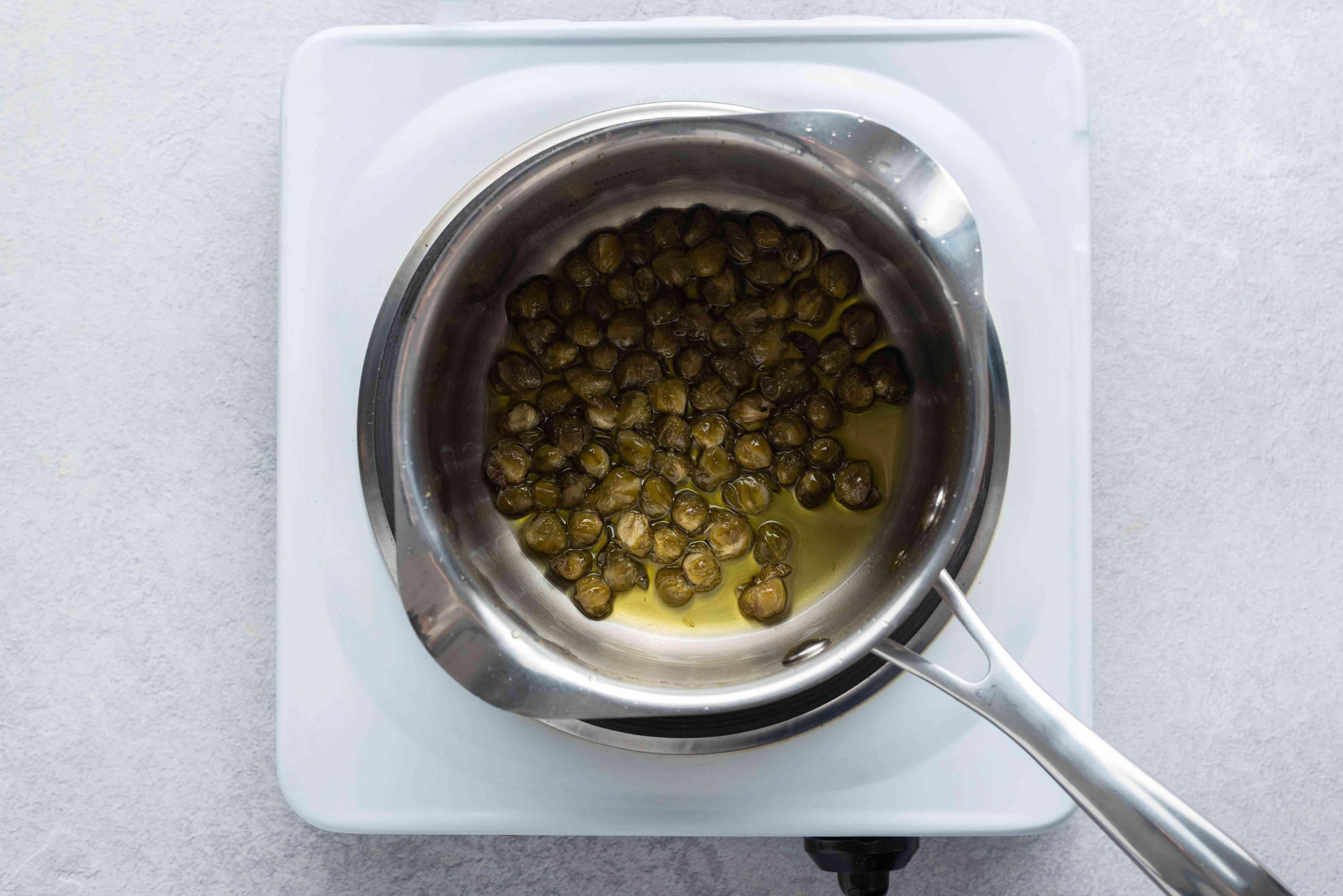 capers and olive oil in a saucepan