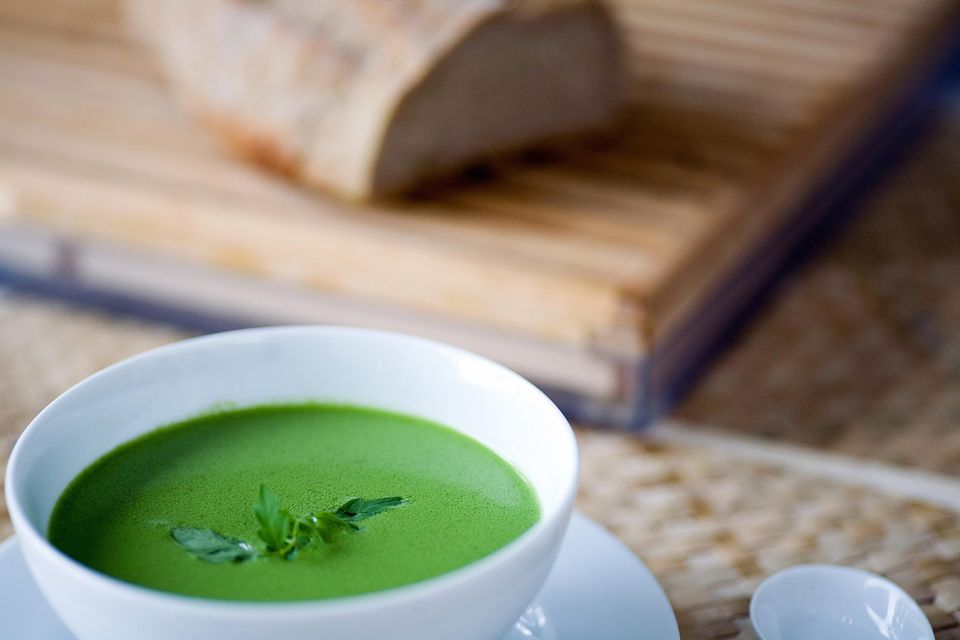Green soup and bread in background