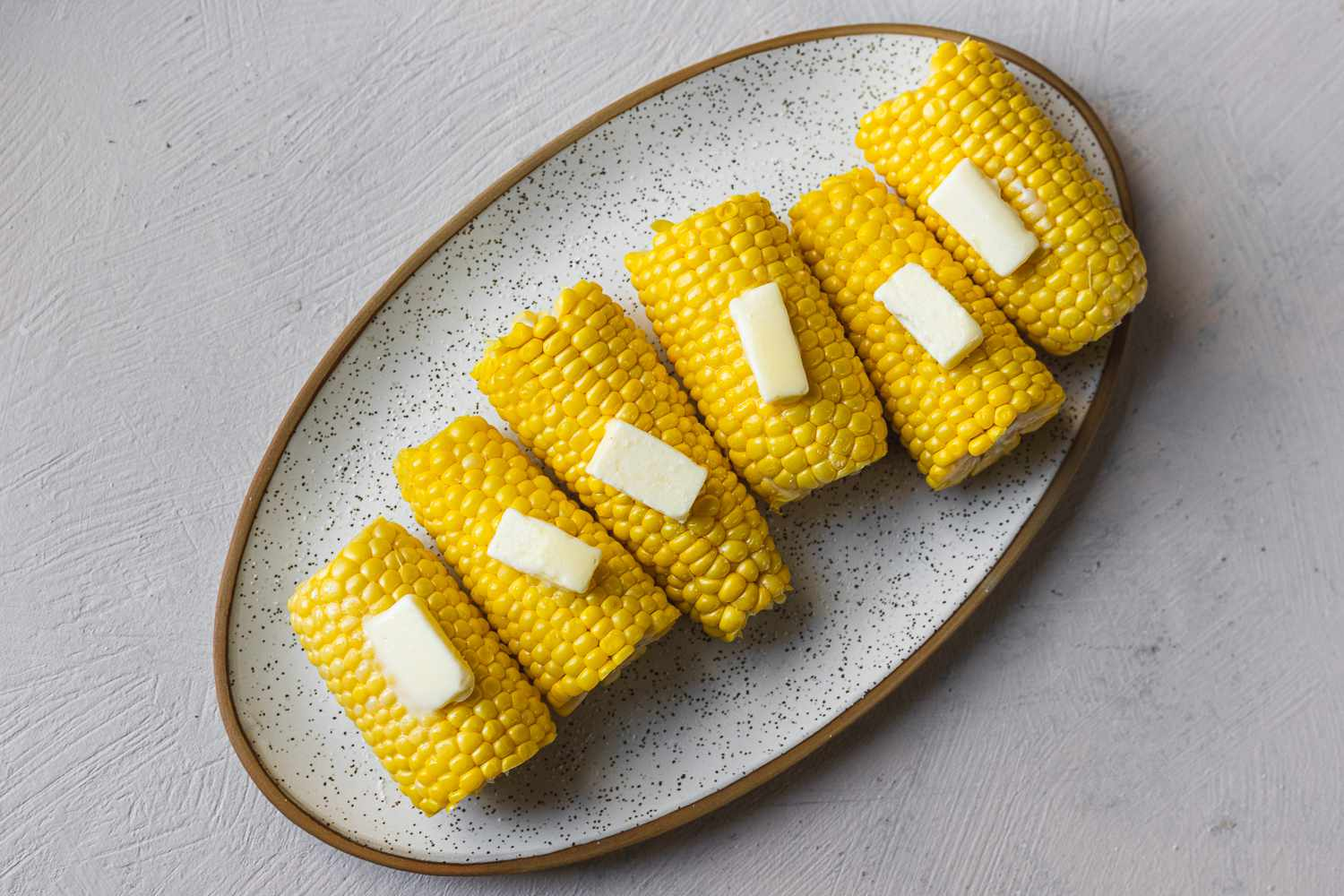 Fresh steamed corn on the cob with pats of butter on a serving plate
