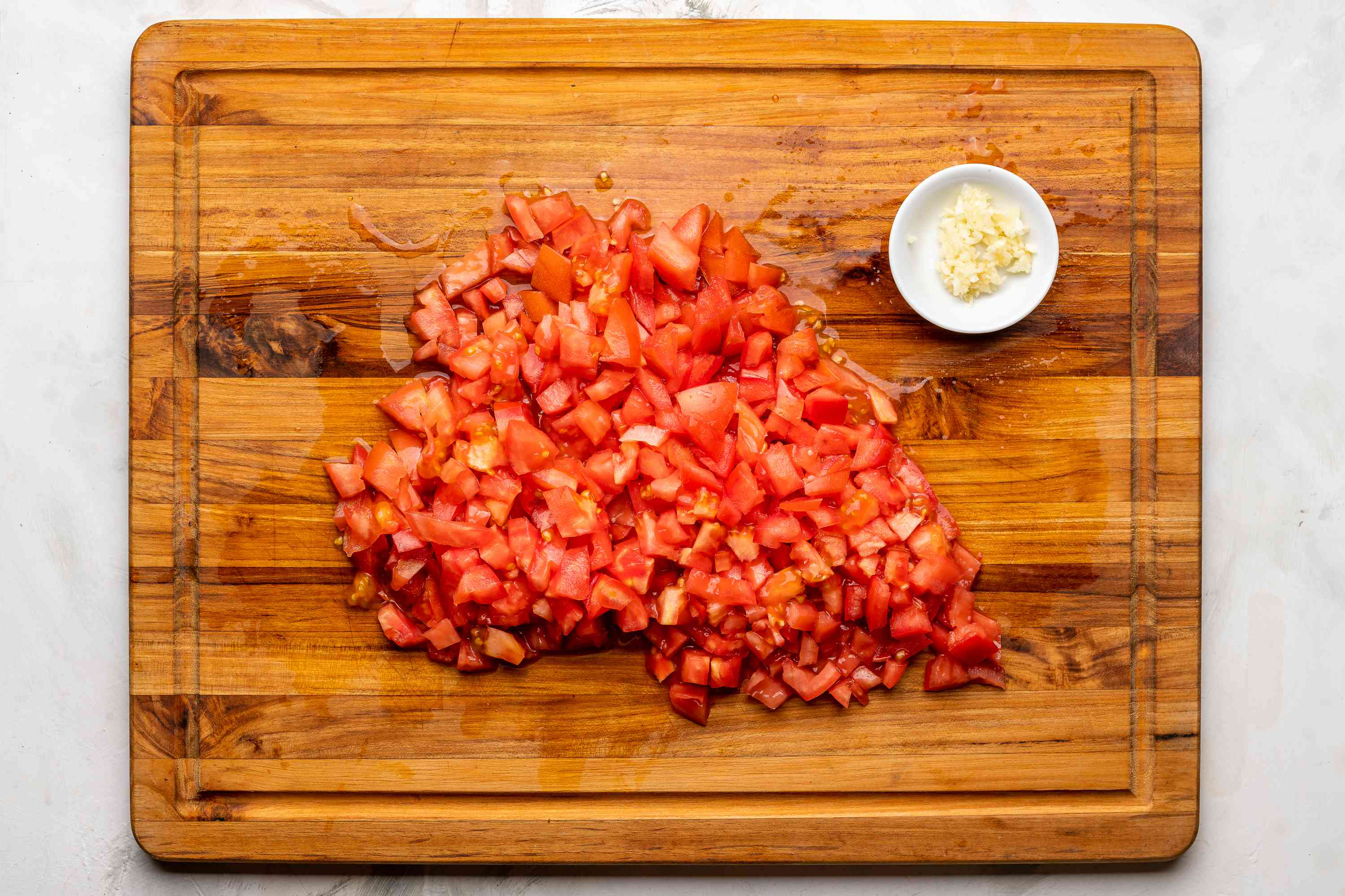 copped tomatoes on a cutting board, garlic in a bowl