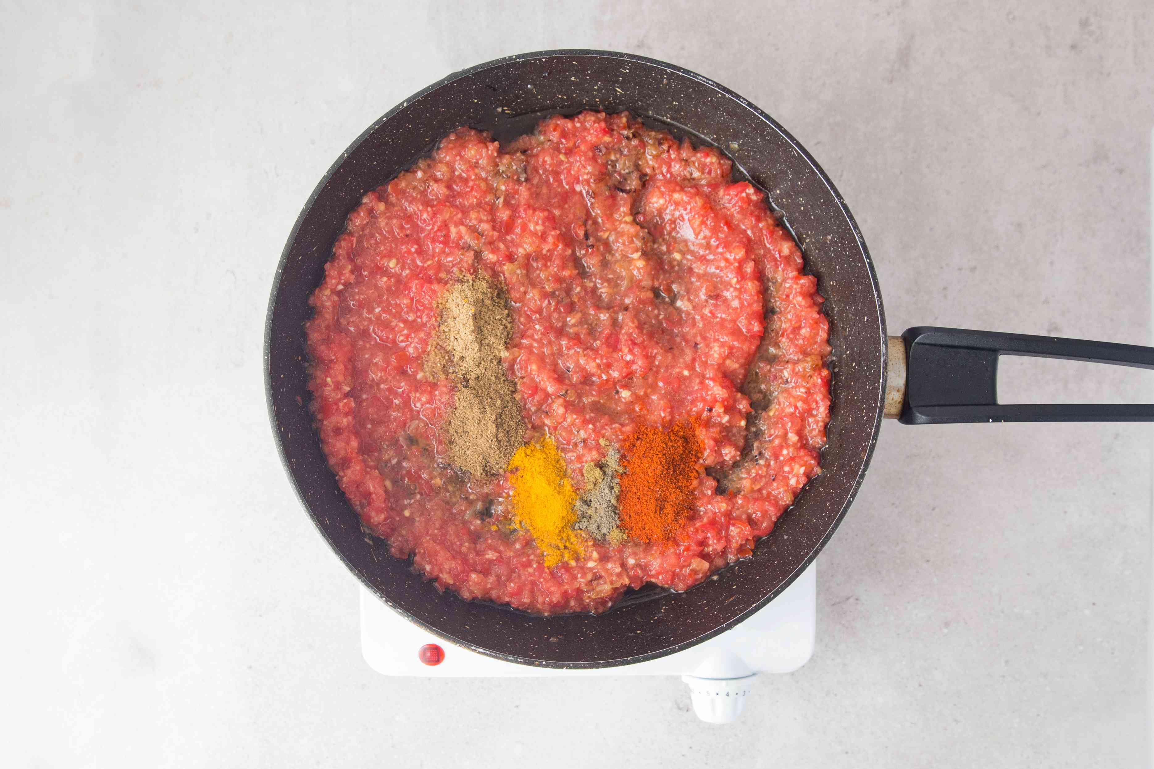 Add tomato mixture, coriander, cumin, turmeric, red chili powder, and garam masala
