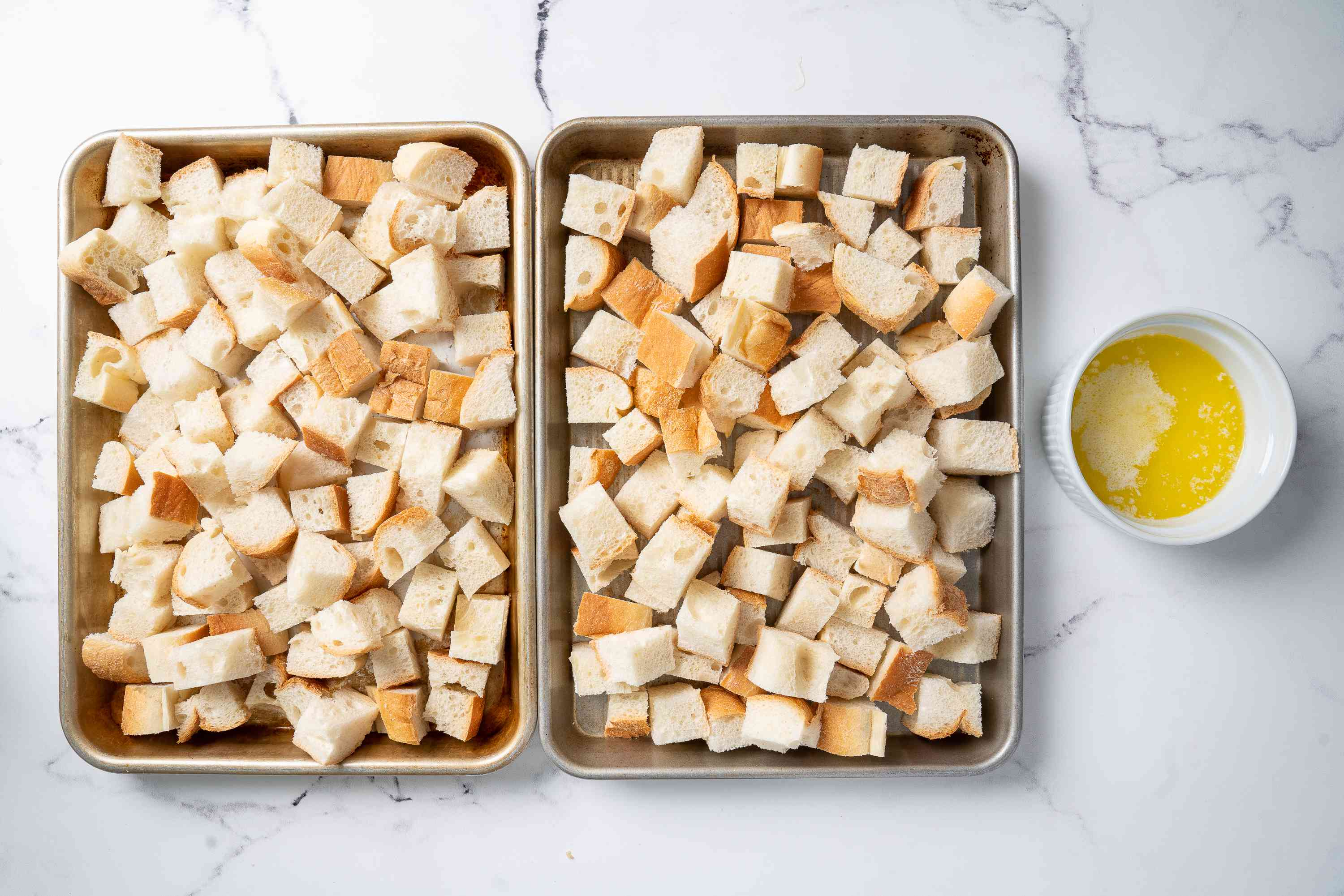Bread cubes on baking sheets with melted butter in a bowl