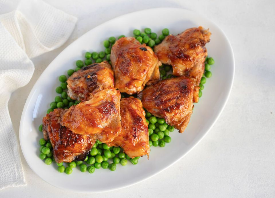 Grilled BBQ chicken thighs served over peas on a white platter